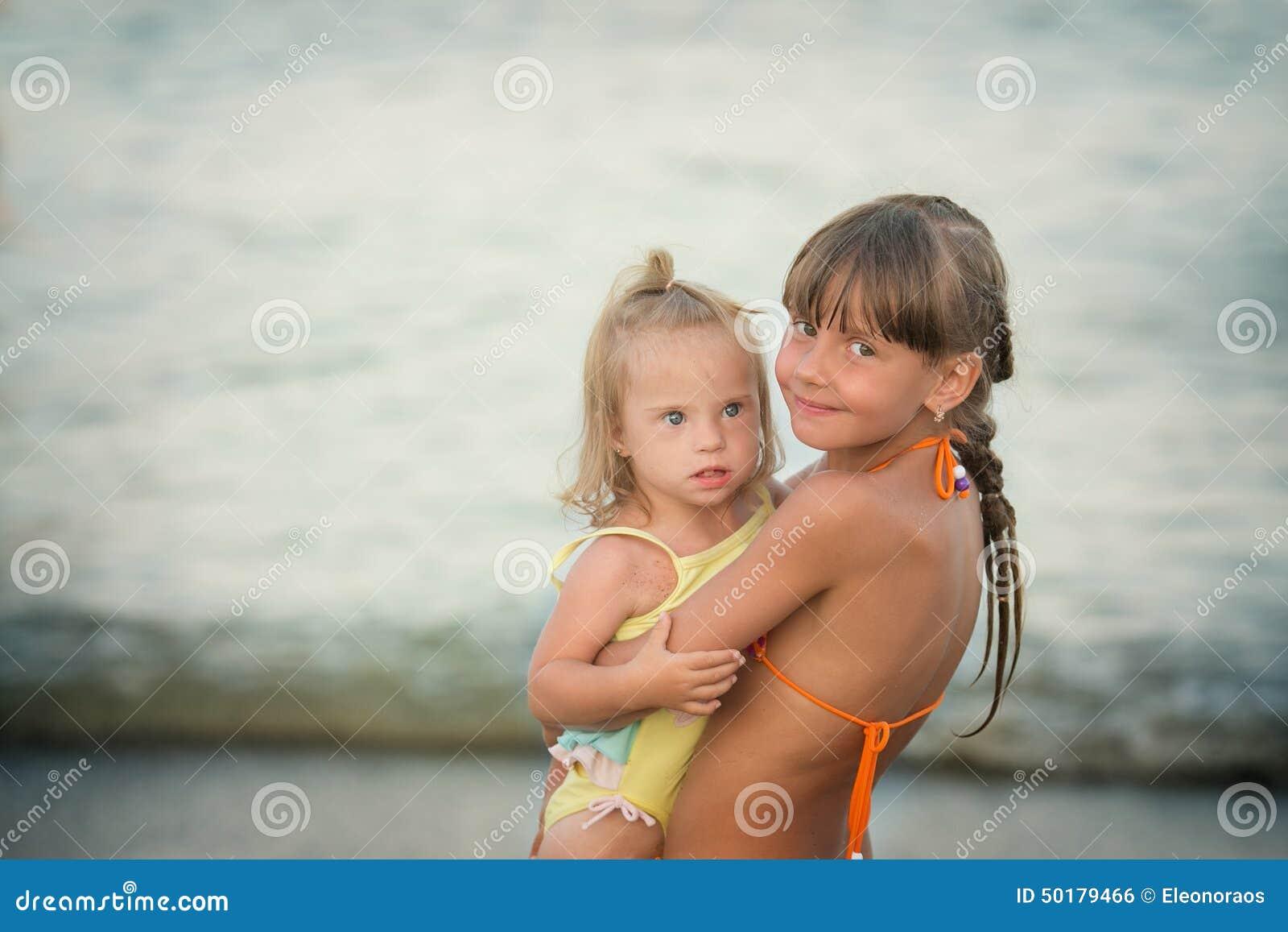 La soeur d épouvantail embrasse affectueusement sa soeur avec la trisomie 21