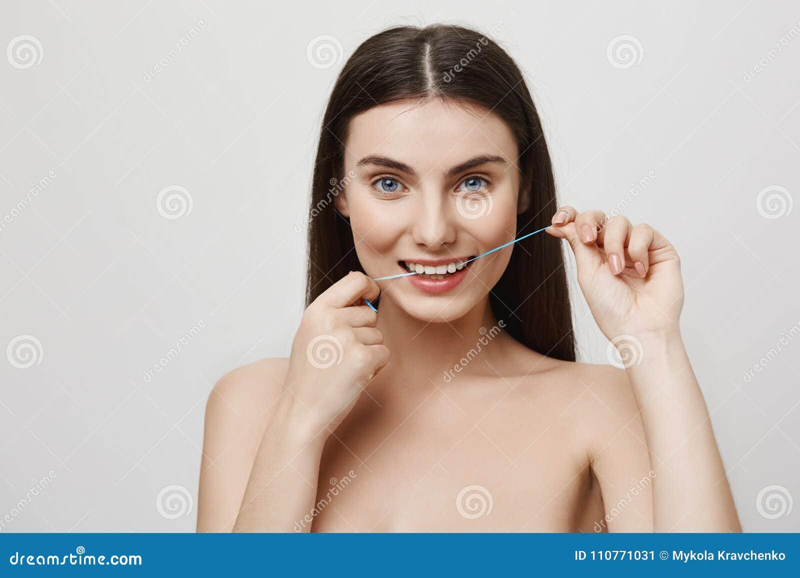 La soie est importante pour le soin de dent Tir d intérieur de femme européenne attirante avec des yeux bleus flossing des dents,