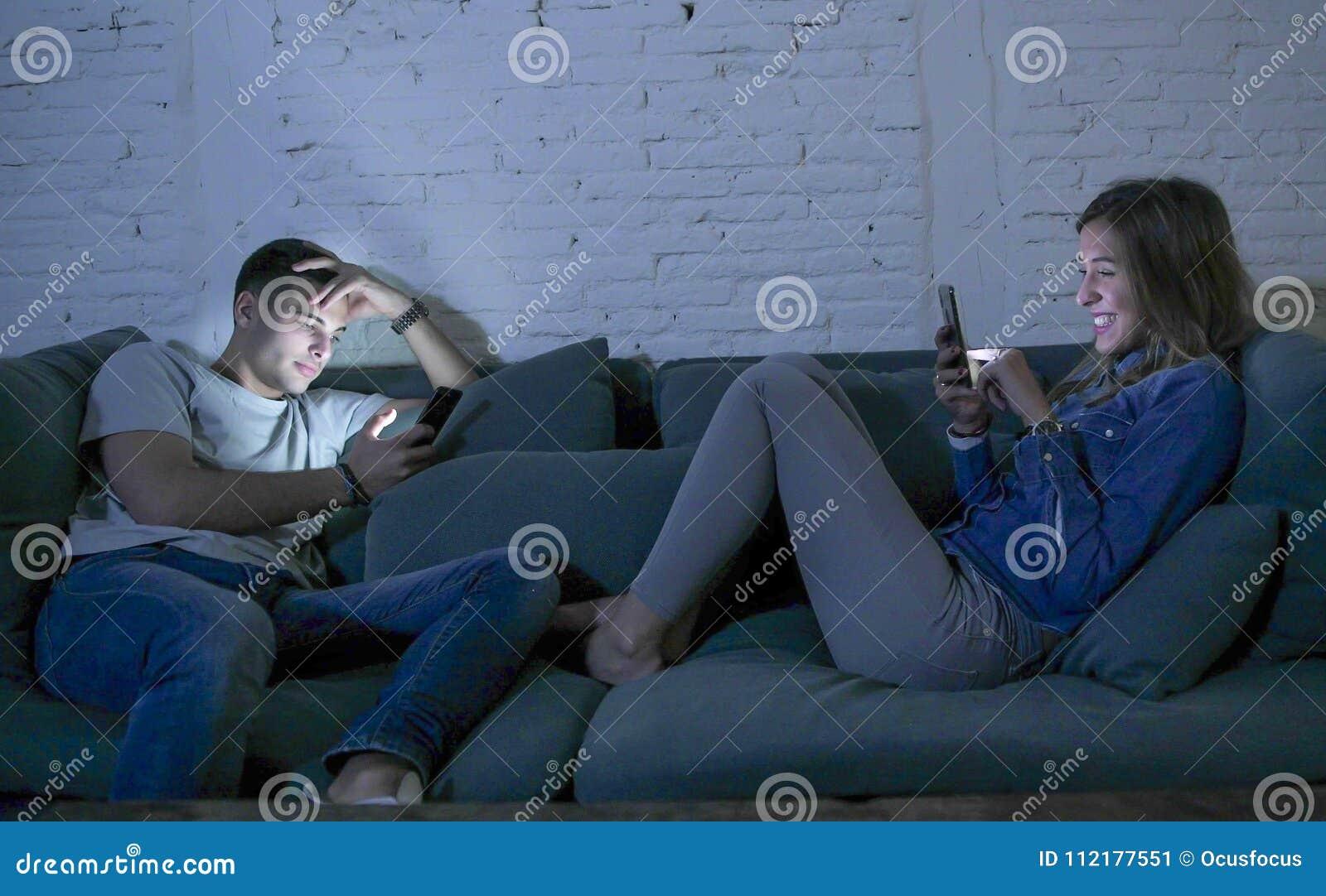 La sonrisa joven del sofá del sofá de los pares en casa feliz junto pero separado ignorándose concentró en el teléfono móvil en I