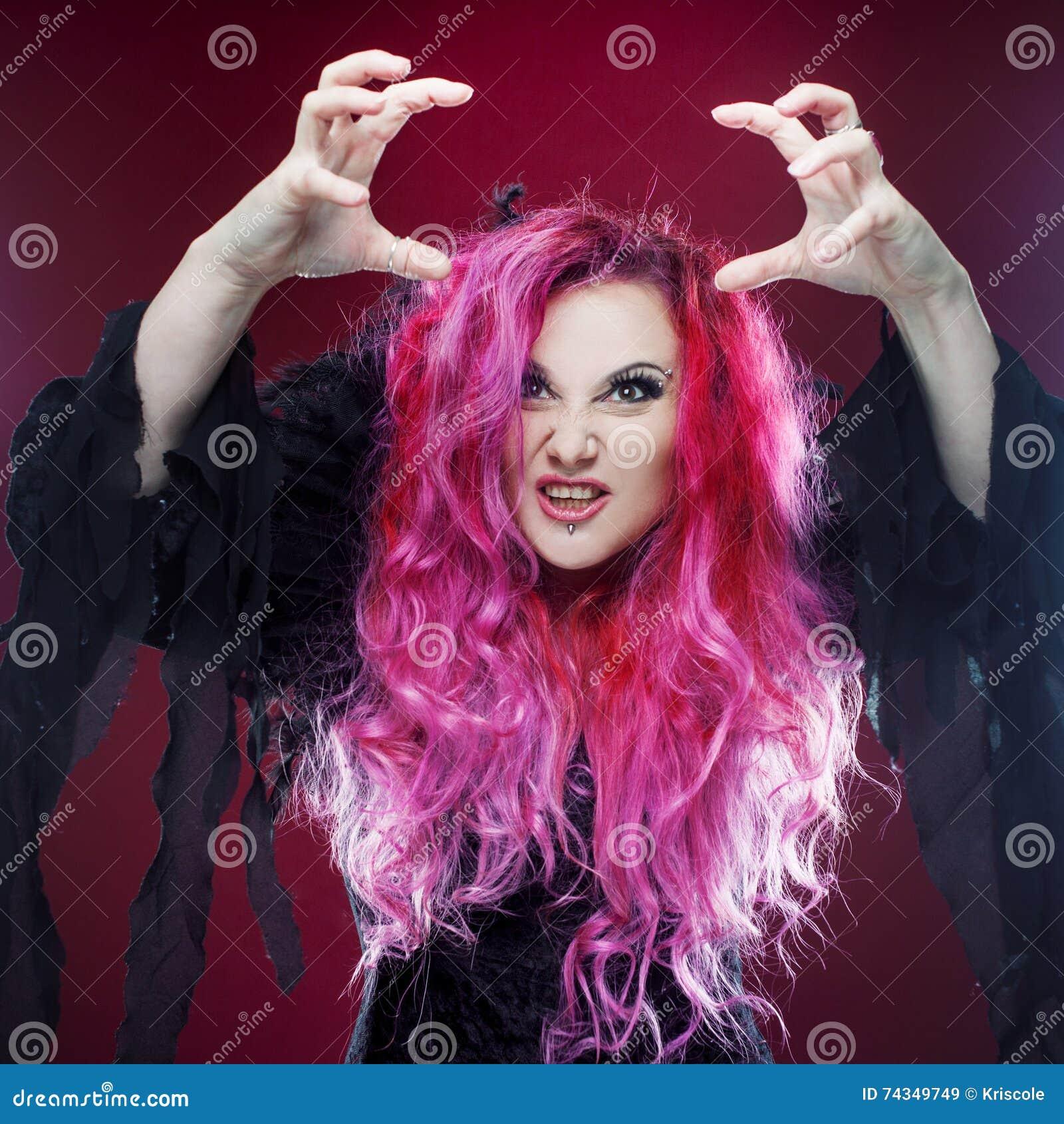 La sorcière effrayante avec les cheveux rouges exécute la magie sur un fond rose Halloween, thème d horreur