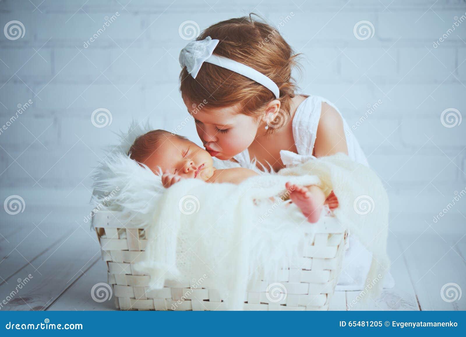 La sorella dei bambini bacia il bambino sonnolento neonato del fratello su una luce