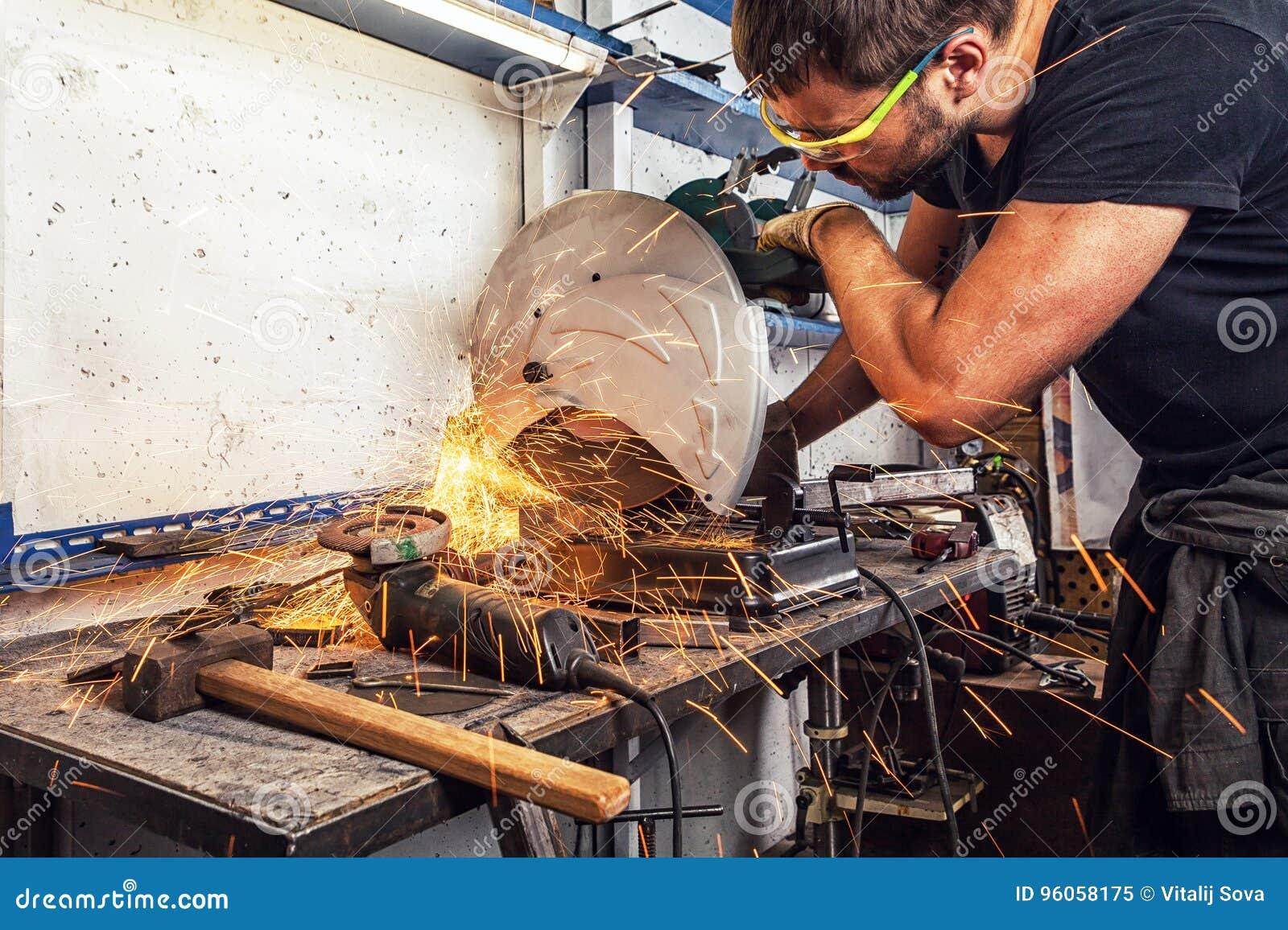 La soudeuse d homme coupe un métal avec une scie circulaire