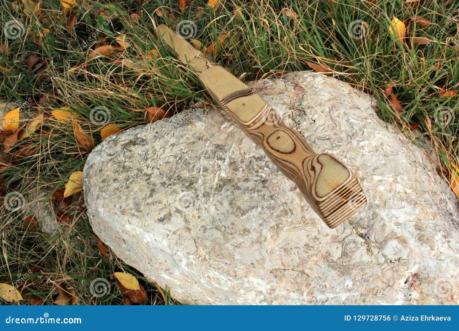 La spada di legno della guaina sta su un supporto su una pietra