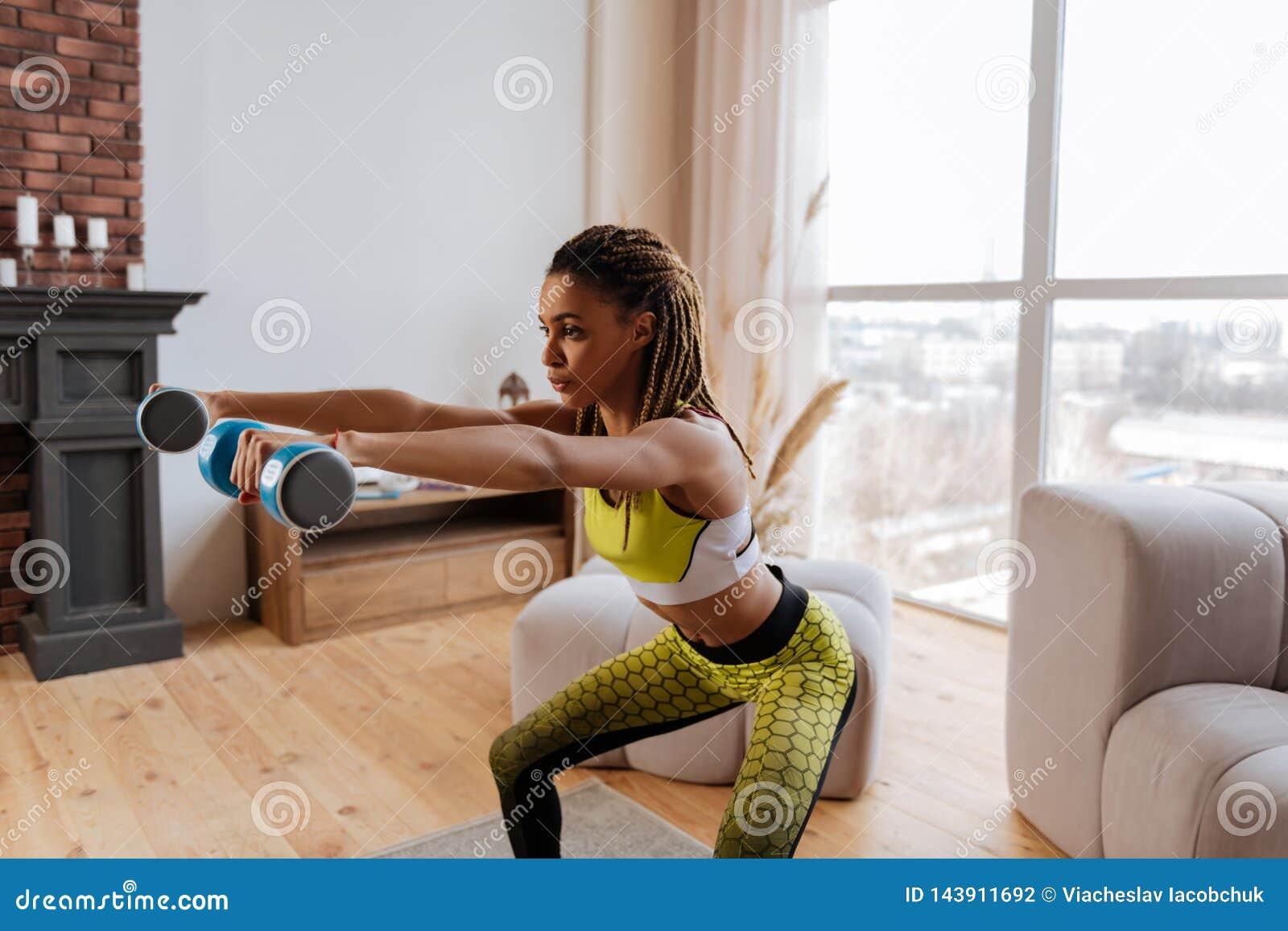 La sportive aux yeux noirs que faire se reposent se lève avec des poids de main à la maison