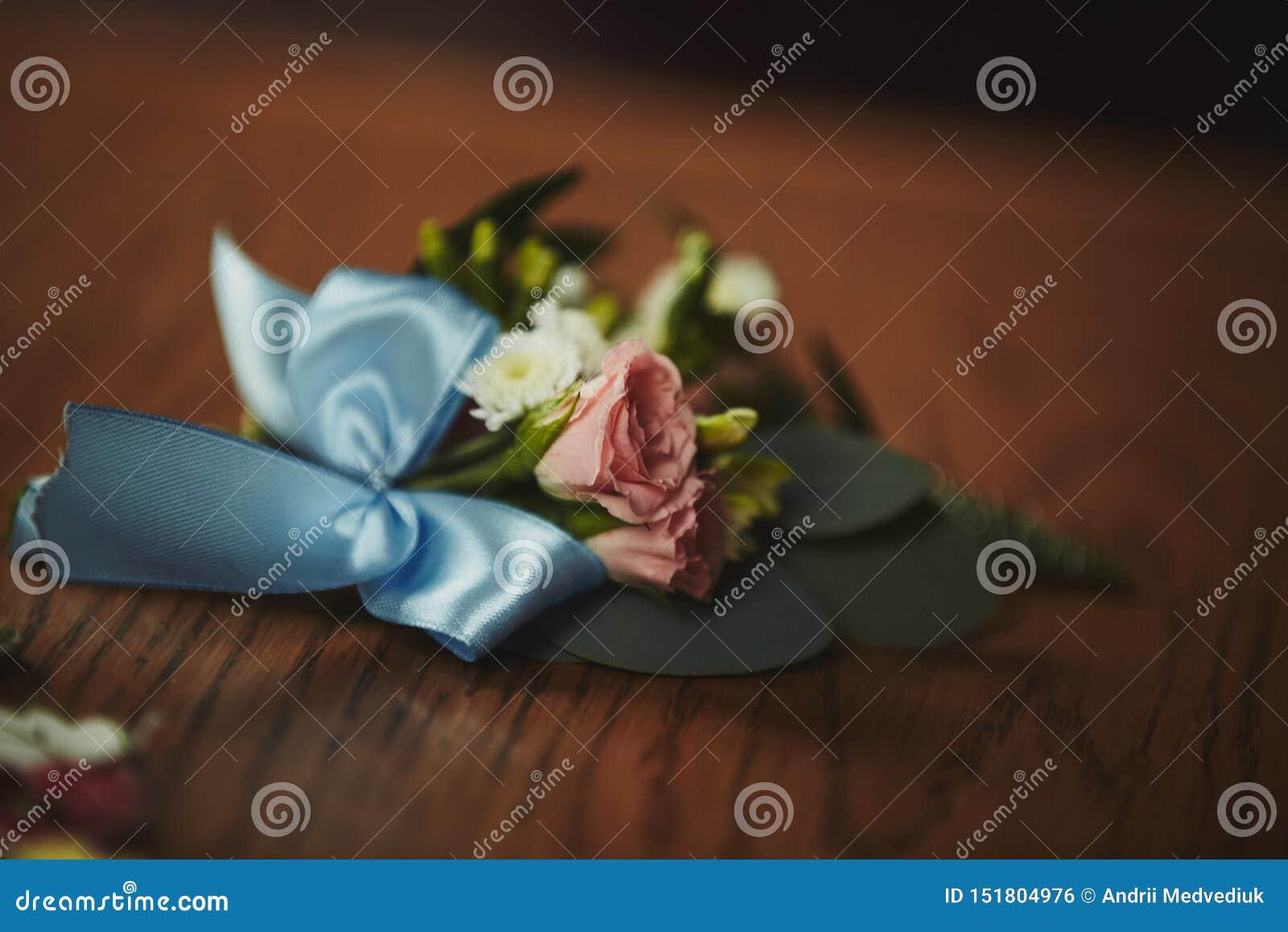 La sposa che tengono a disposizione primo piano i fiori dell occhiello dello sposo con le rose bianche e verde e pianta