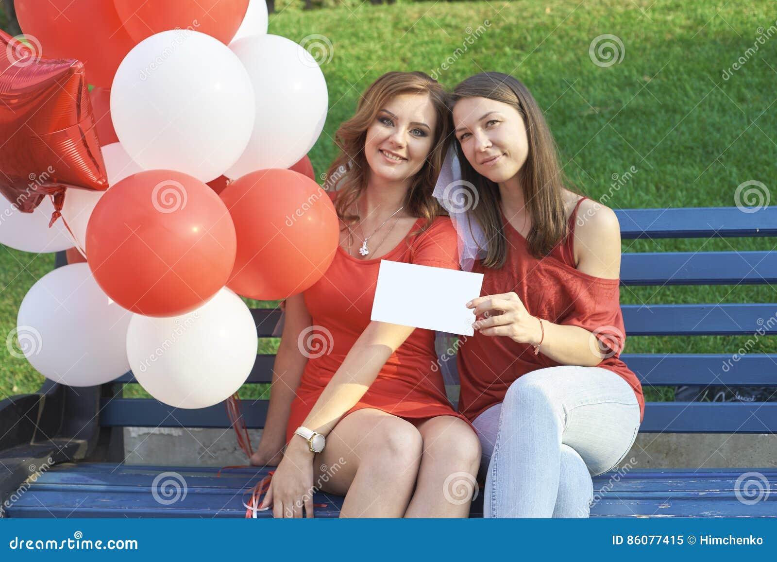 La sposa con la sua amica che si siede nel parco Tenga i palloni