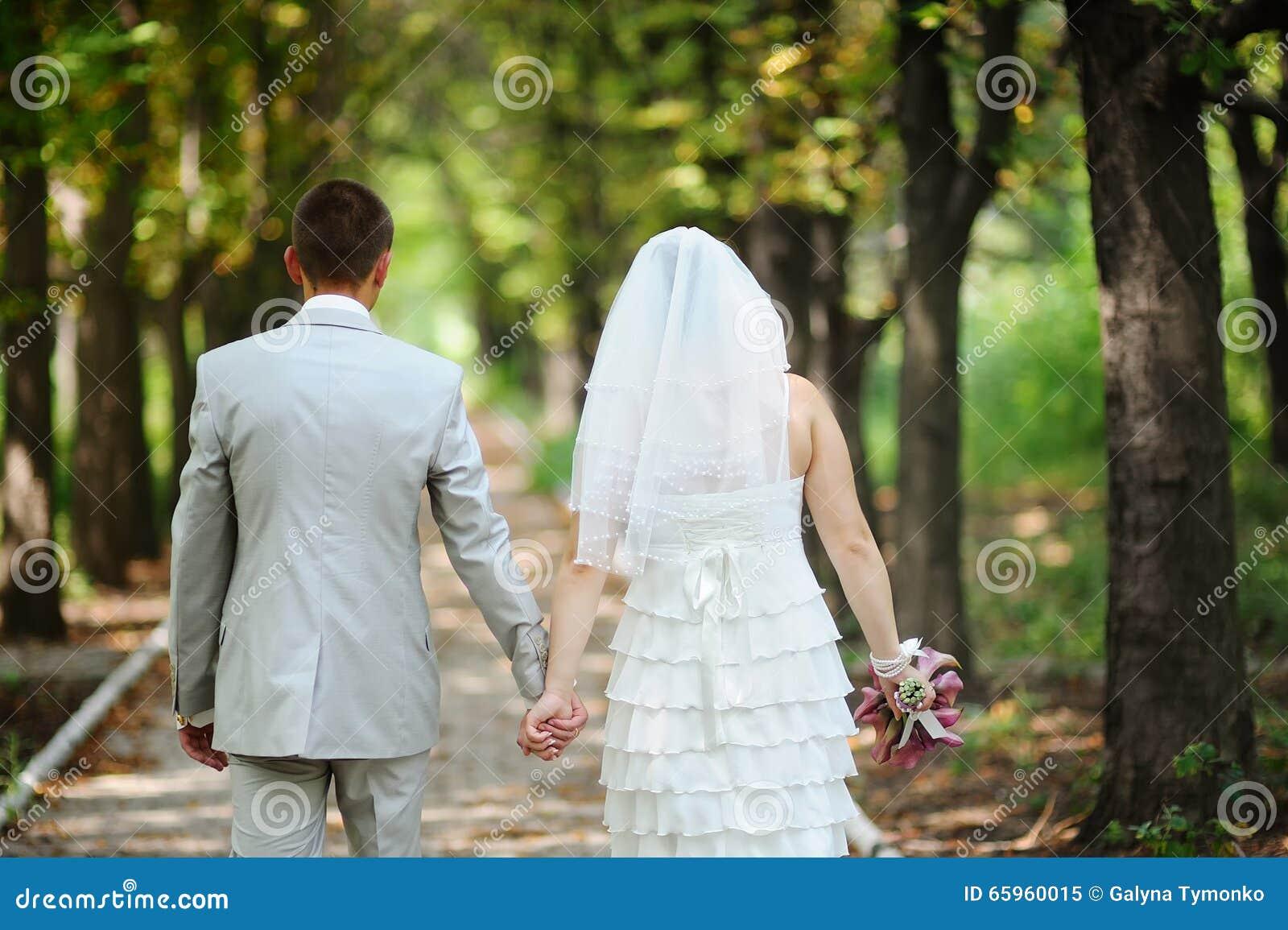 La sposa e lo sposo che si allontanano di estate parcheggiano all aperto