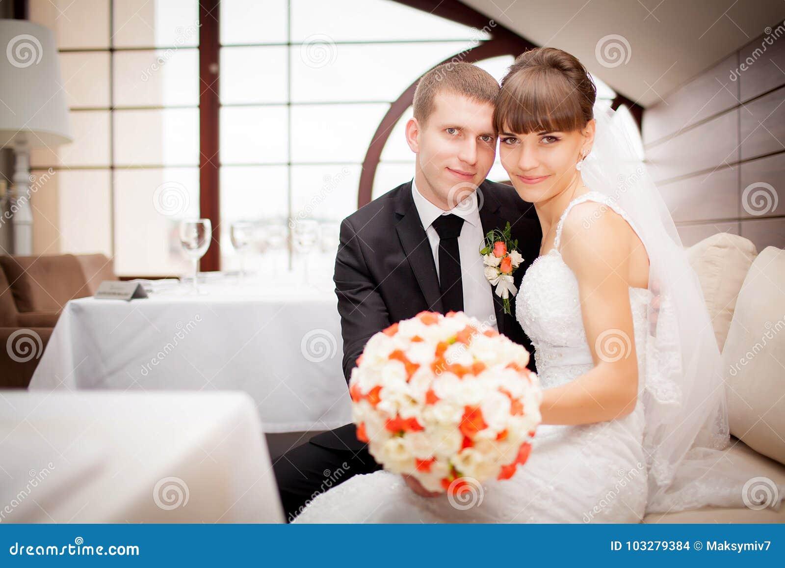 La sposa e lo sposo felici sulle nozze camminano nell hotel moderno ha