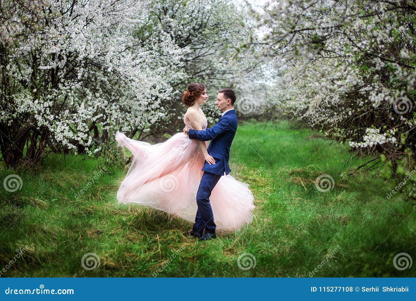 La sposa e lo sposo in vestiti da sposa contro il contesto dei giardini di fioritura