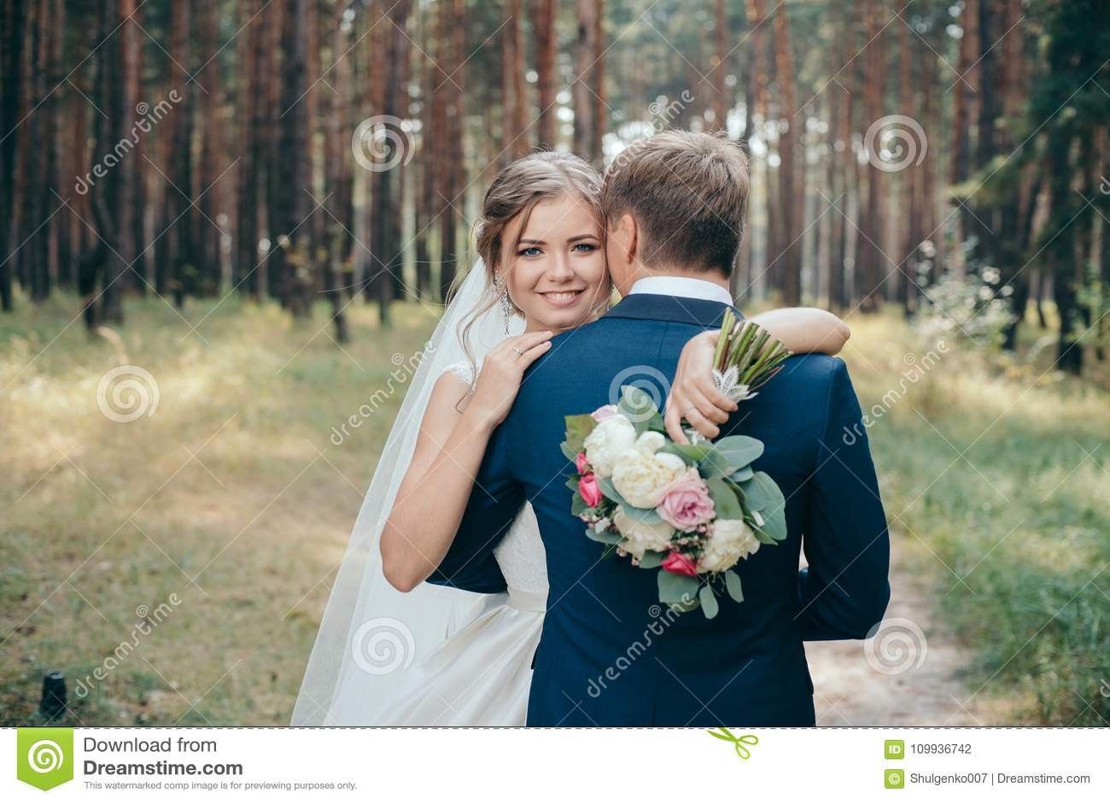 La sposa e lo sposo in vestiti da sposa su sfondo naturale Giorno delle nozze Le persone appena sposate stanno camminando attrave