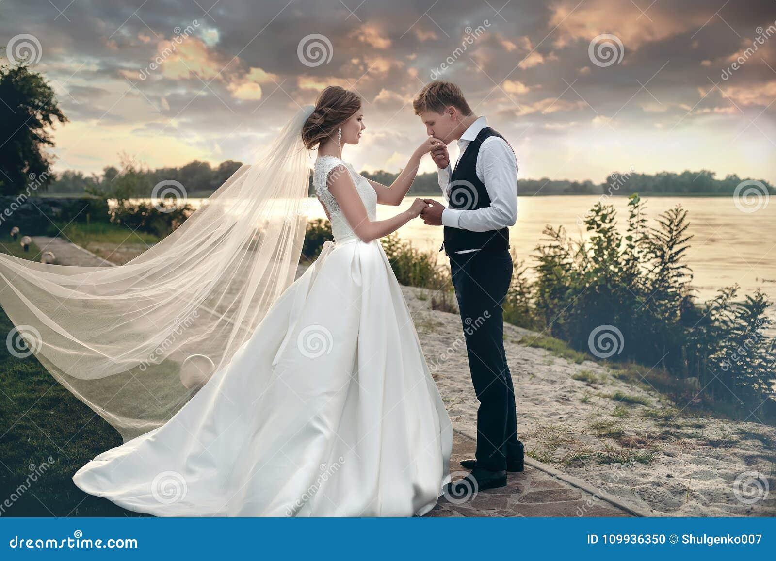 La sposa e lo sposo in vestiti da sposa su sfondo naturale Ne