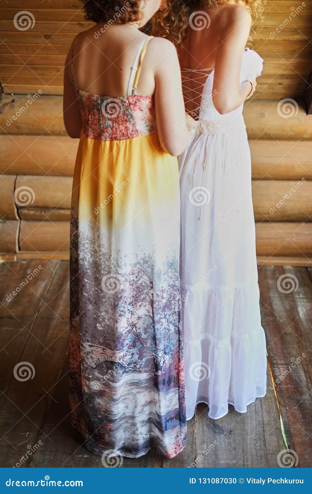 La sposa sta fissando un vestito da sposa la damigella d onore aiuta la sposa che l amica aiuta la sposa