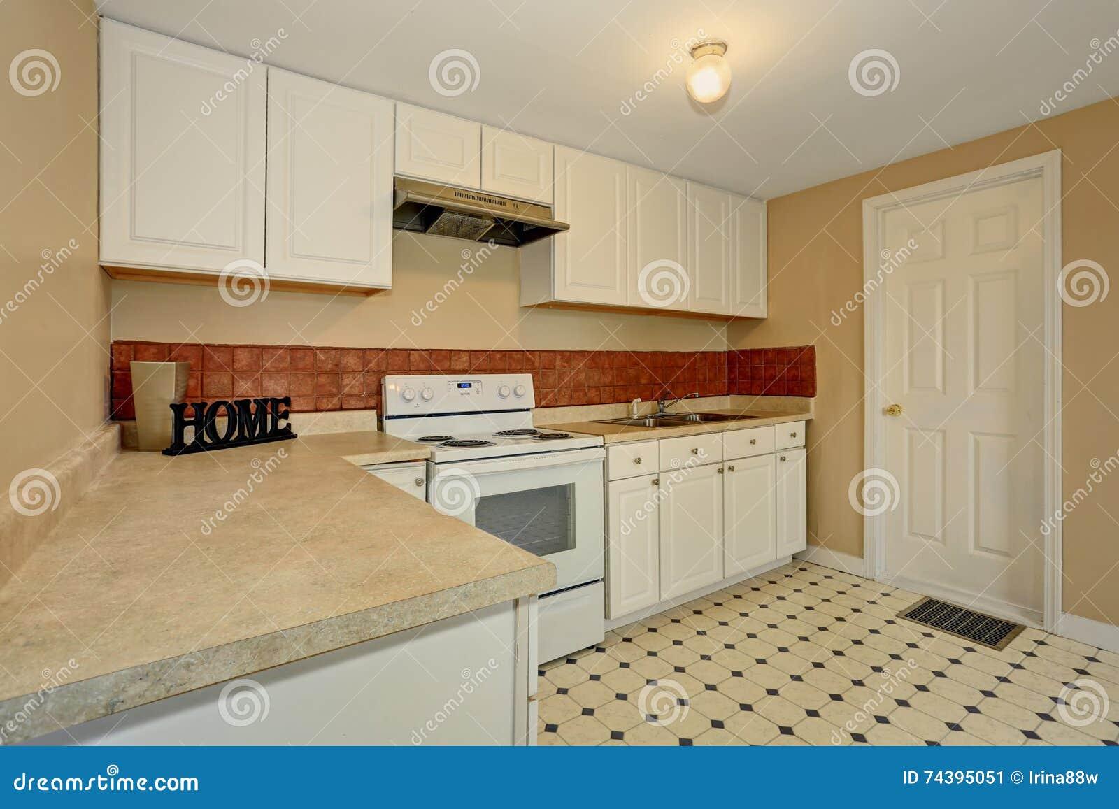 La stanza bianca della cucina con la pavimentazione in piastrelle