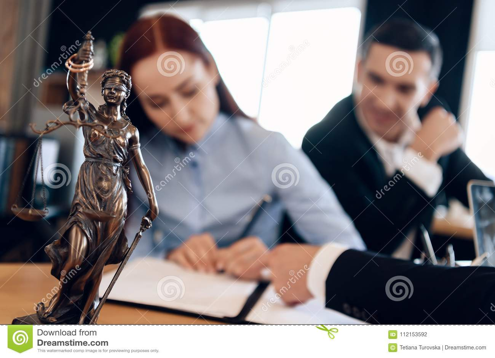 La statua bronzea di Themis tiene la bilancia della giustizia Nel fondo unfocused, l adulto firma i documenti