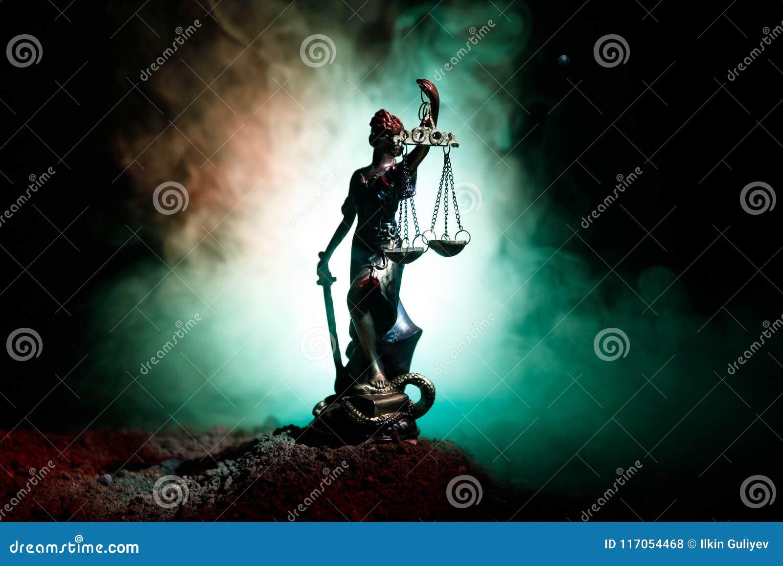 La statue de la justice - justice ou Iustitia/Justitia de dame la déesse romaine de la justice sur un fond foncé du feu