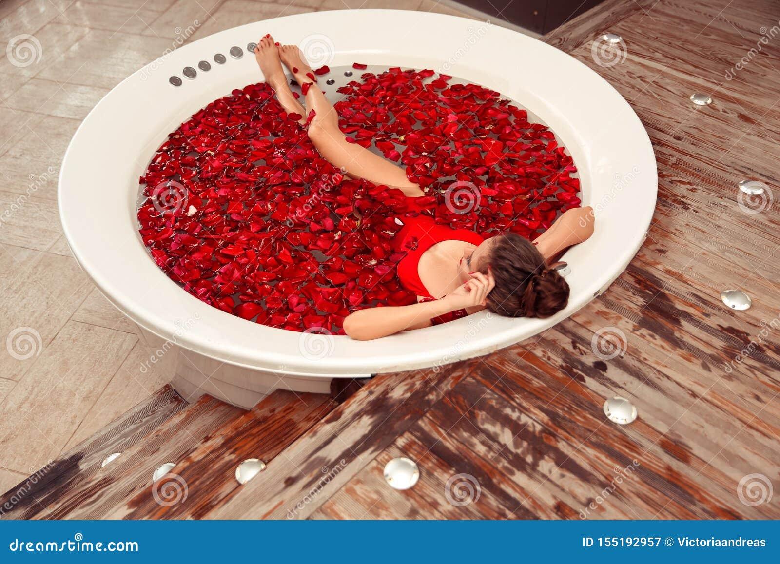 La stazione termale si distende Bella donna del bikini che si trova nella Jacuzzi rotonda con i petali di rosa rossa Salute e bel