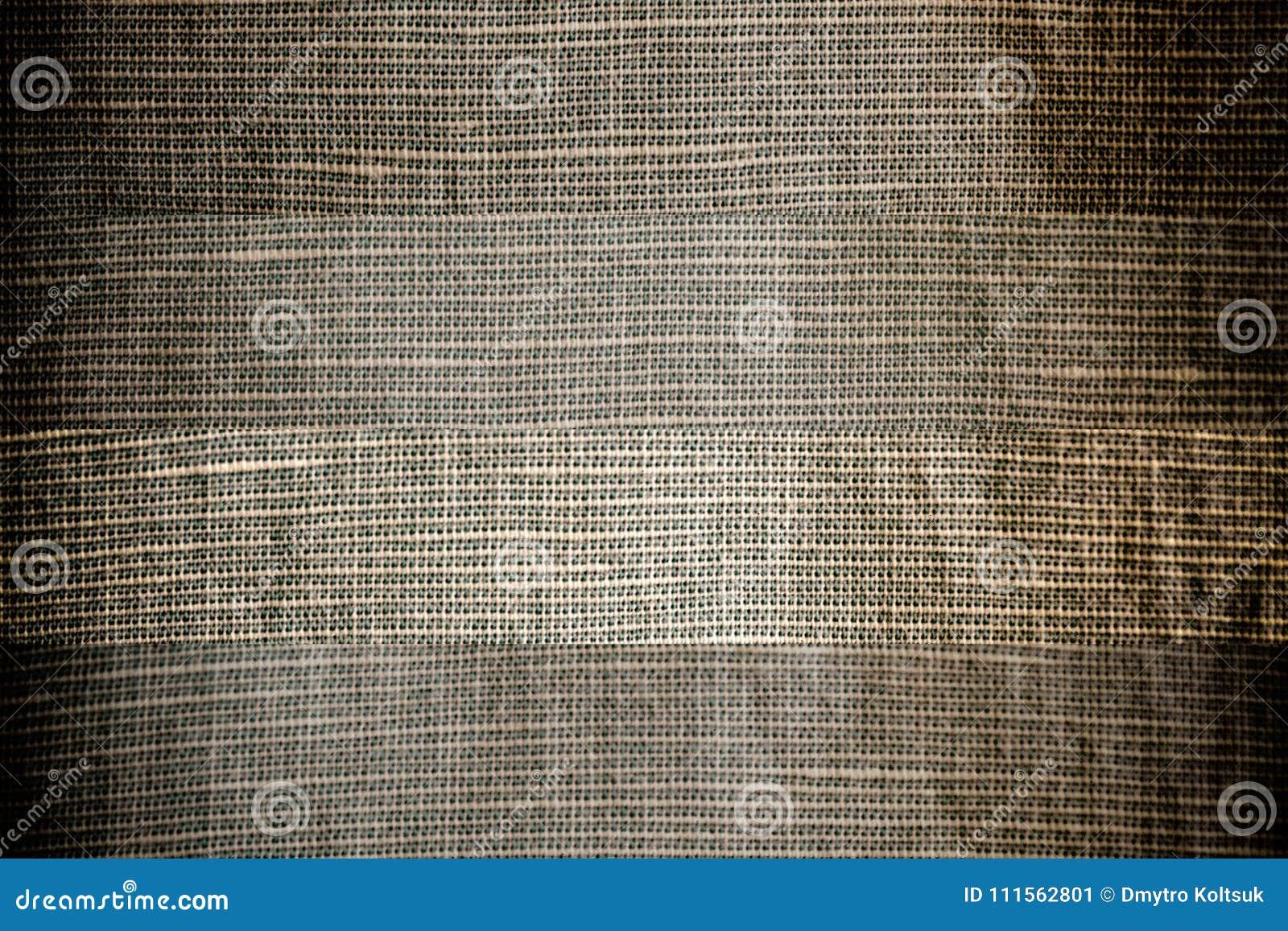 La struttura o il fondo di tela grigia neutrale del primo piano, linea differente ha separato il tessuto