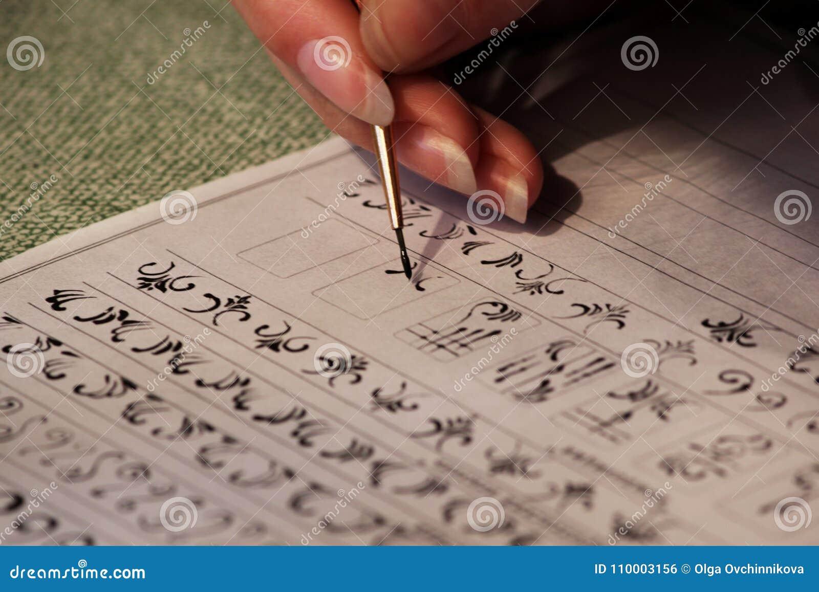 La studentessa impara disegnare i monogrammi per il disegno loro sulle unghie quando crea un manicure con la gomma lacca della la