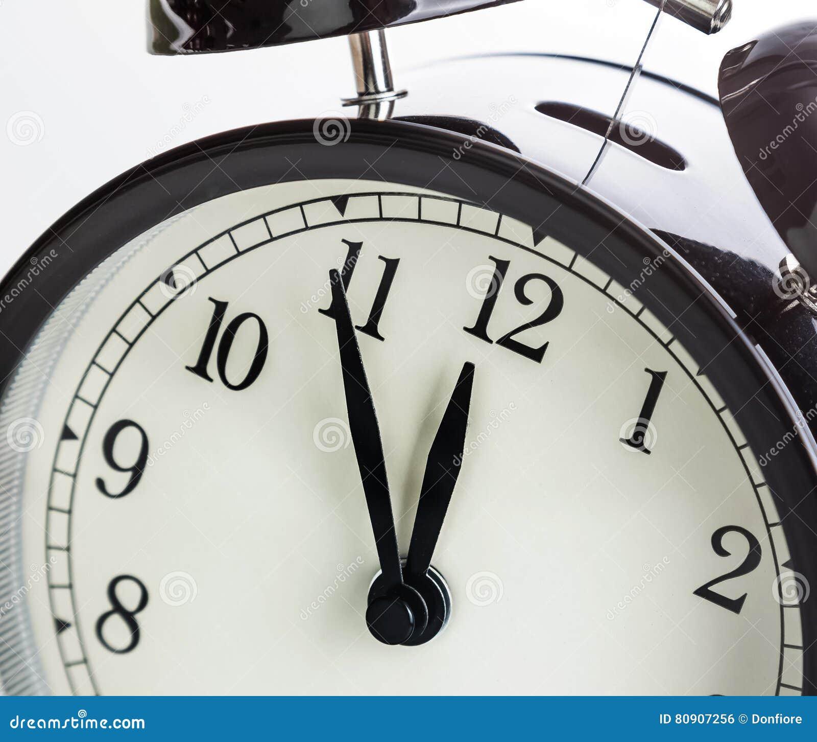 La sveglia sta mostrando il mezzogiorno o la mezzanotte È orologio del ` di dodici o, buon anno di festa festivo o concetto del p