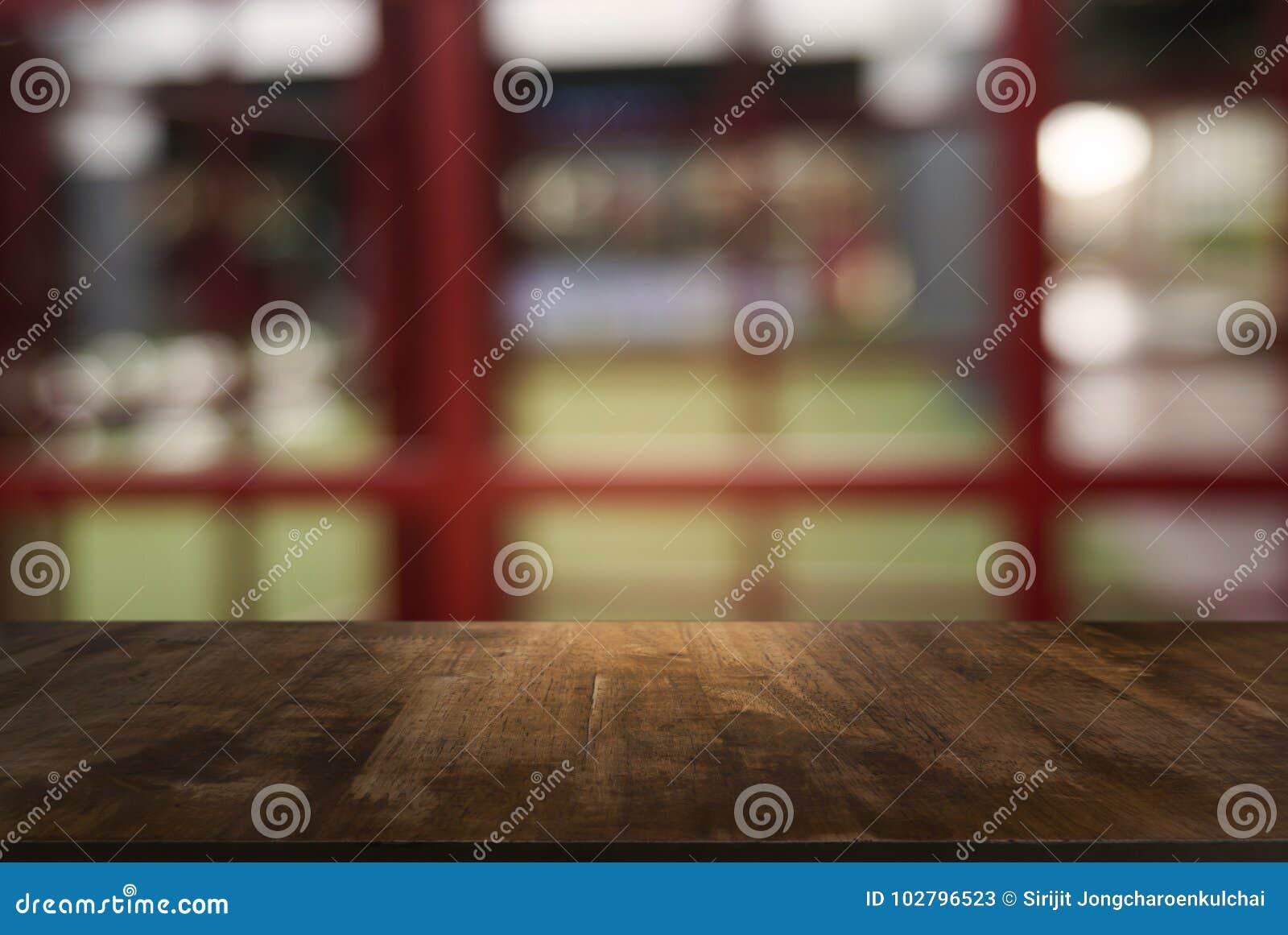 La tabla de madera oscura vacía delante del extracto empañó el fondo