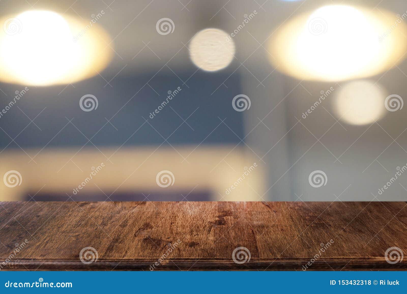 La tabla de madera oscura vac?a delante del extracto empa?? el fondo del bokeh del restaurante