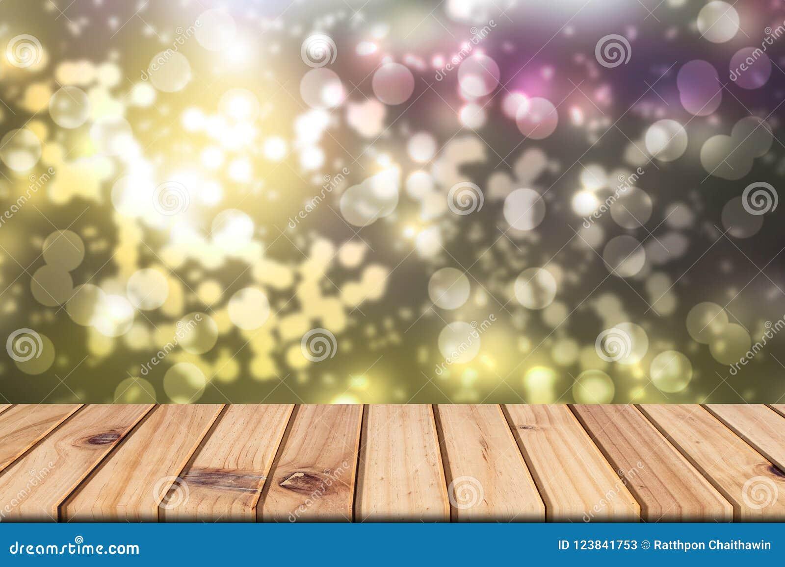 La tabla de madera vacía en frente empañó el fondo colorido del bokeh