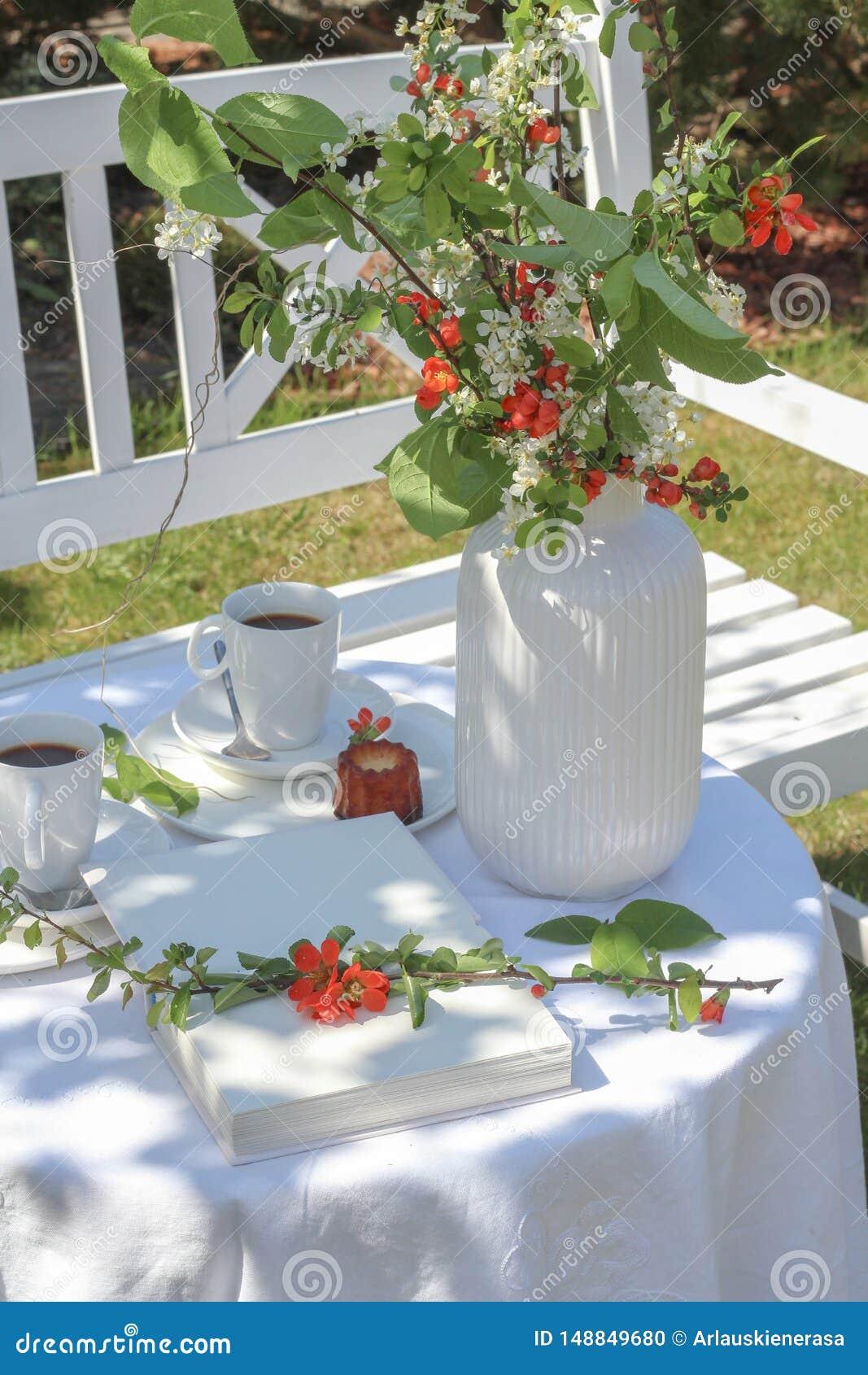 La table blanche avec du café, des caneles et des fleurs a servi dans le jardin