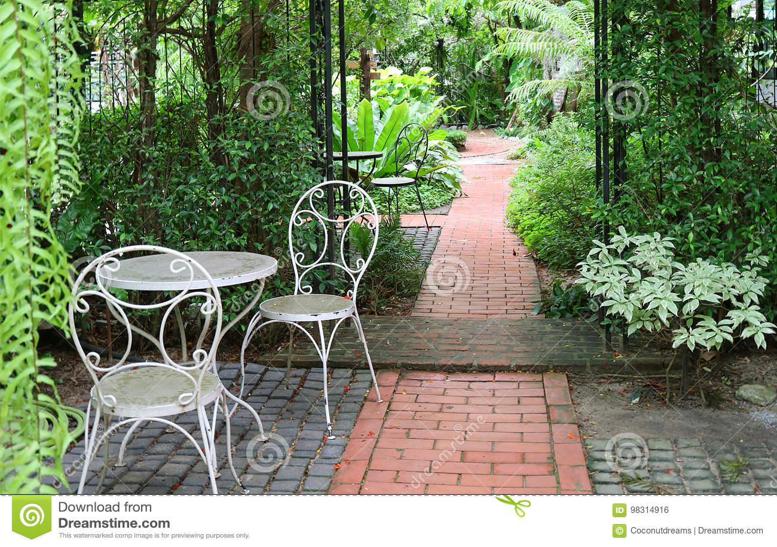 La Table Blanche Et Les Chaises De Fer Travaillé Dans Le Jardin ...
