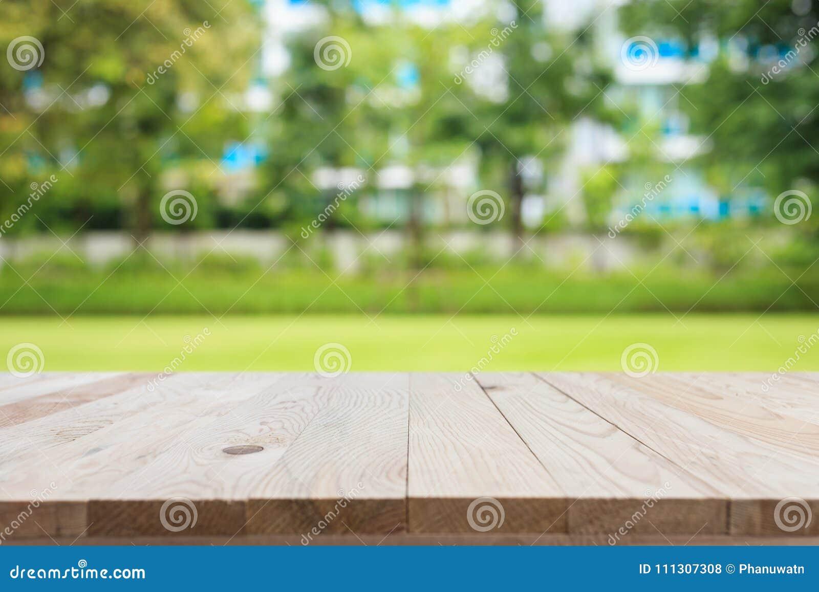 La table en bois supérieure vide et le résumé ensoleillé ont brouillé le backgrou de bokeh