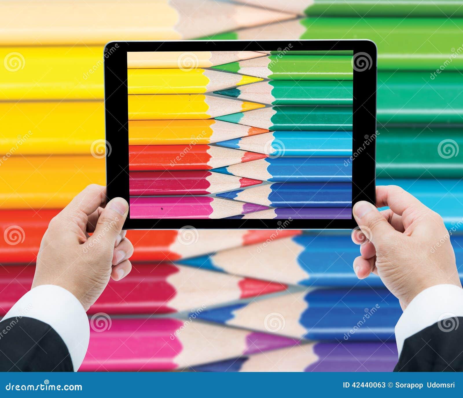 La tableta de las manos del hombre de negocios que toma imágenes cerca encima del color dibujó a lápiz