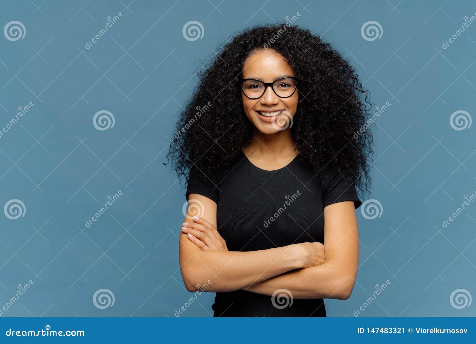 La taille a tiré de la femme afro-américaine de sourire fait plier des bras, porte des lunettes et le T-shirt noir occasionnel, a