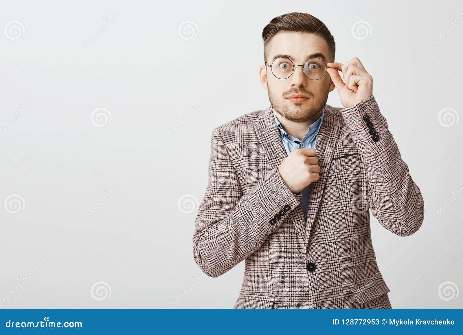 La taille- a tiré du ballot masculin timide et peu sûr mignon dans les verres et la veste de fantaisie tenant le poing près des y