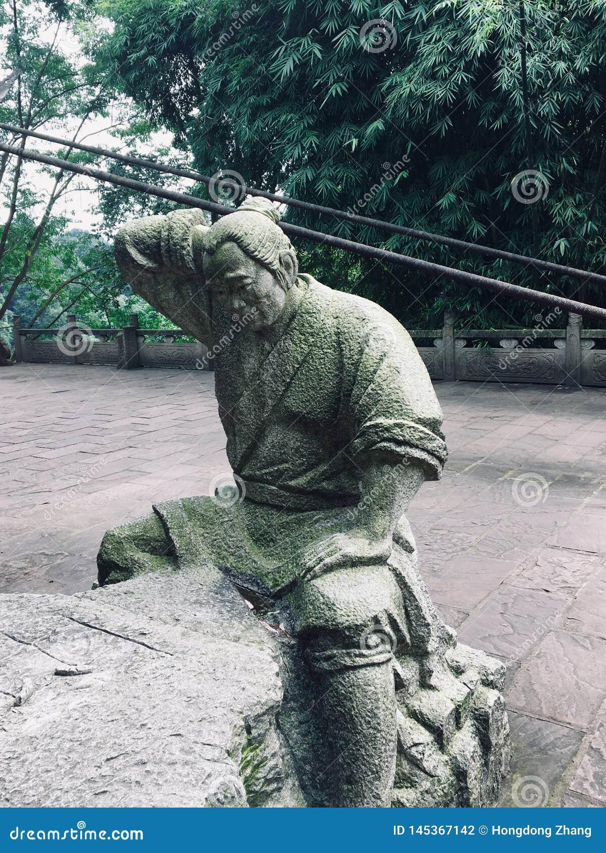 La talla de piedra del granjero que está pensando en cómo jugar a ajedrez