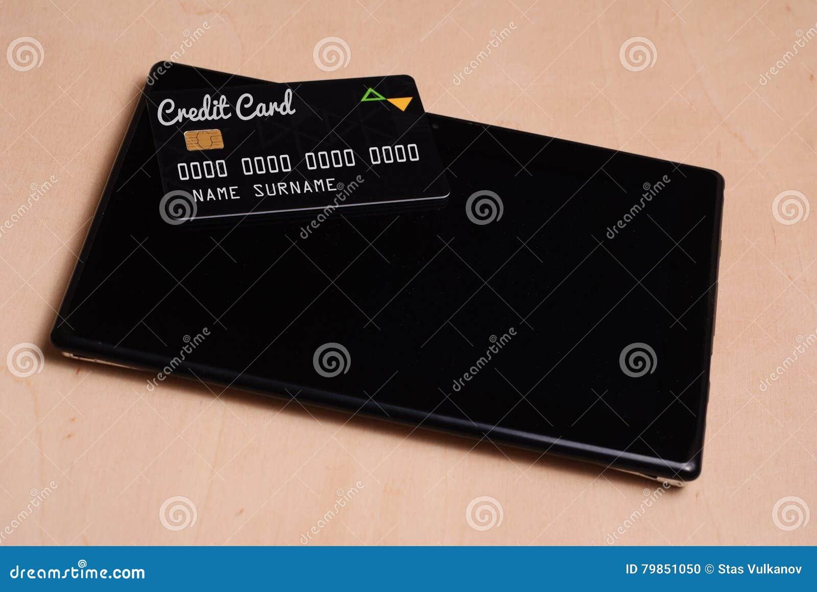 La tarjeta de crédito negra está en una tableta electrónica negra,