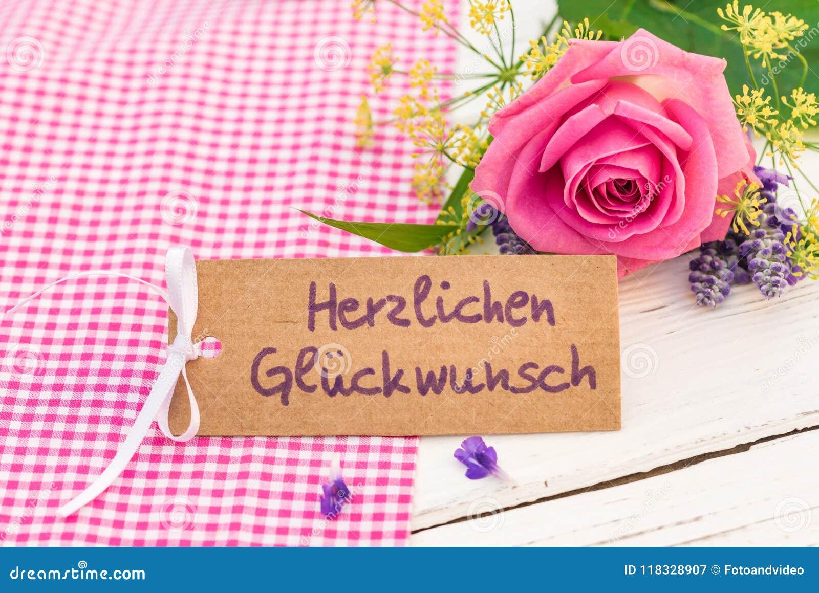 La tarjeta de la enhorabuena con el texto alemán, Herzlichen Glueckwunsch, la enhorabuena de los medios y la rosa del rosa florec