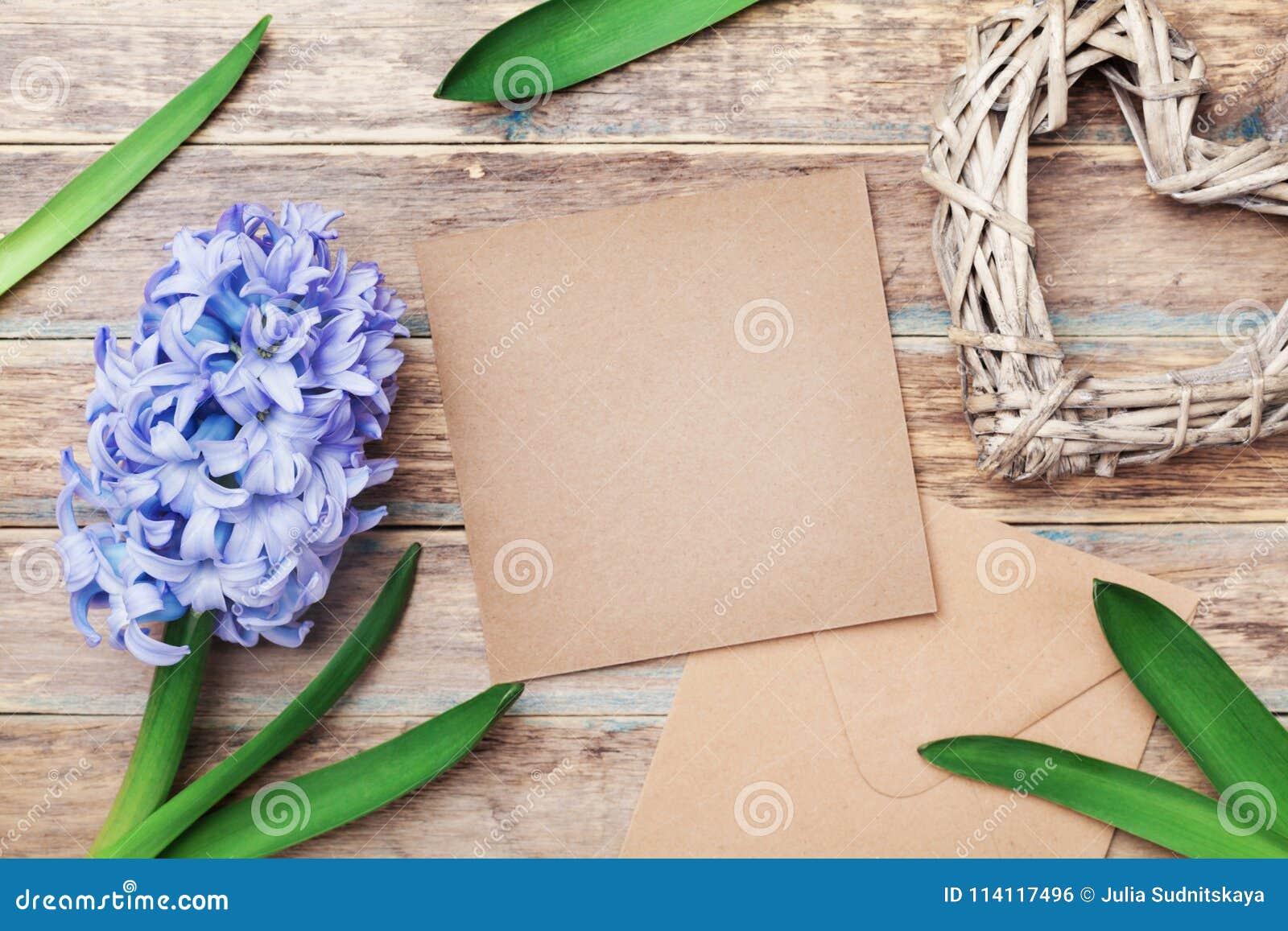 La tarjeta de felicitación el día de madres con el sobre de Kraft adornó las flores y el corazón del jacinto en fondo rústico Vis