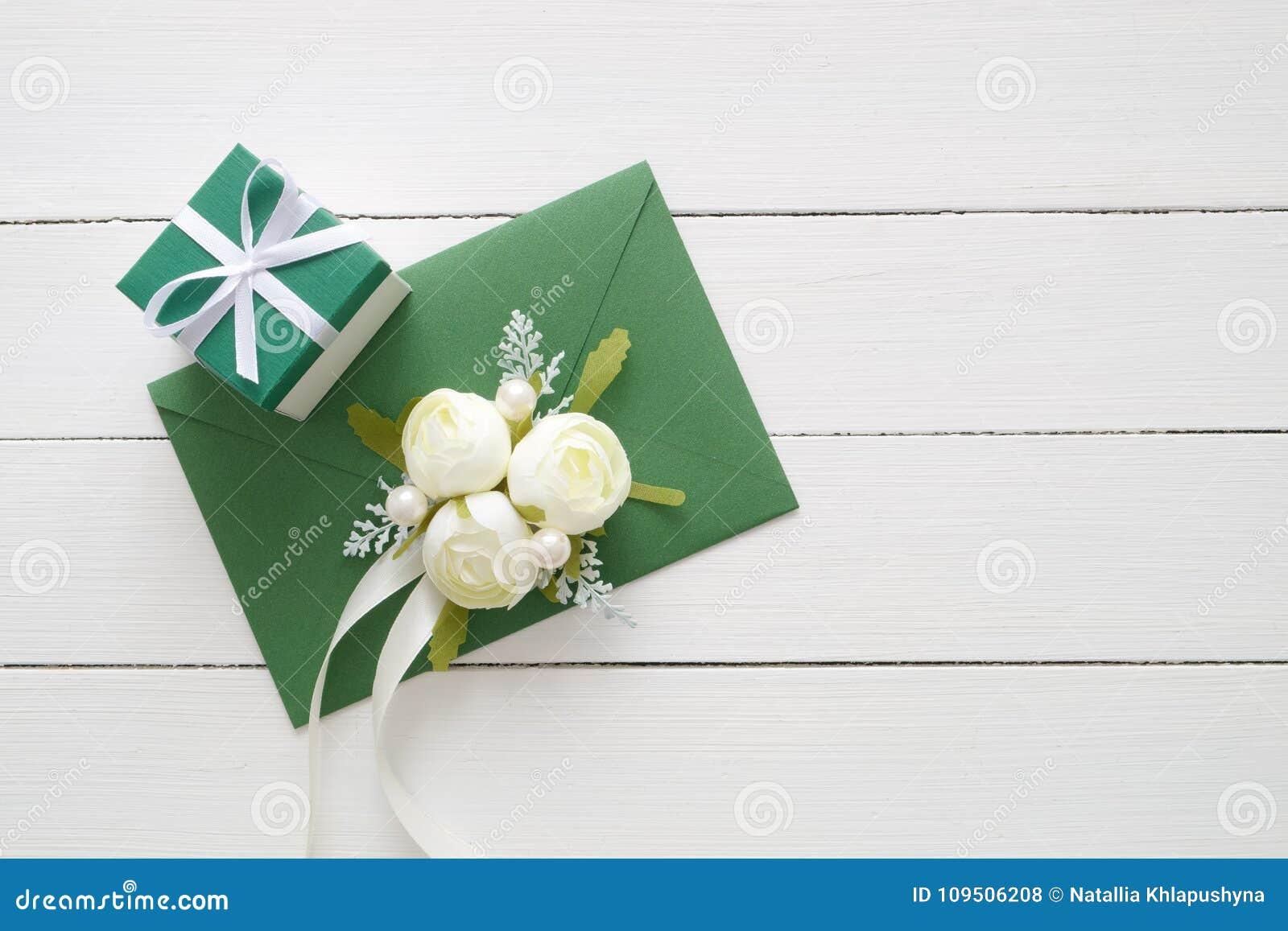 La tarjeta de la invitación de la boda o la letra de día de las tarjetas del día de San Valentín en el sobre verde adornado con l