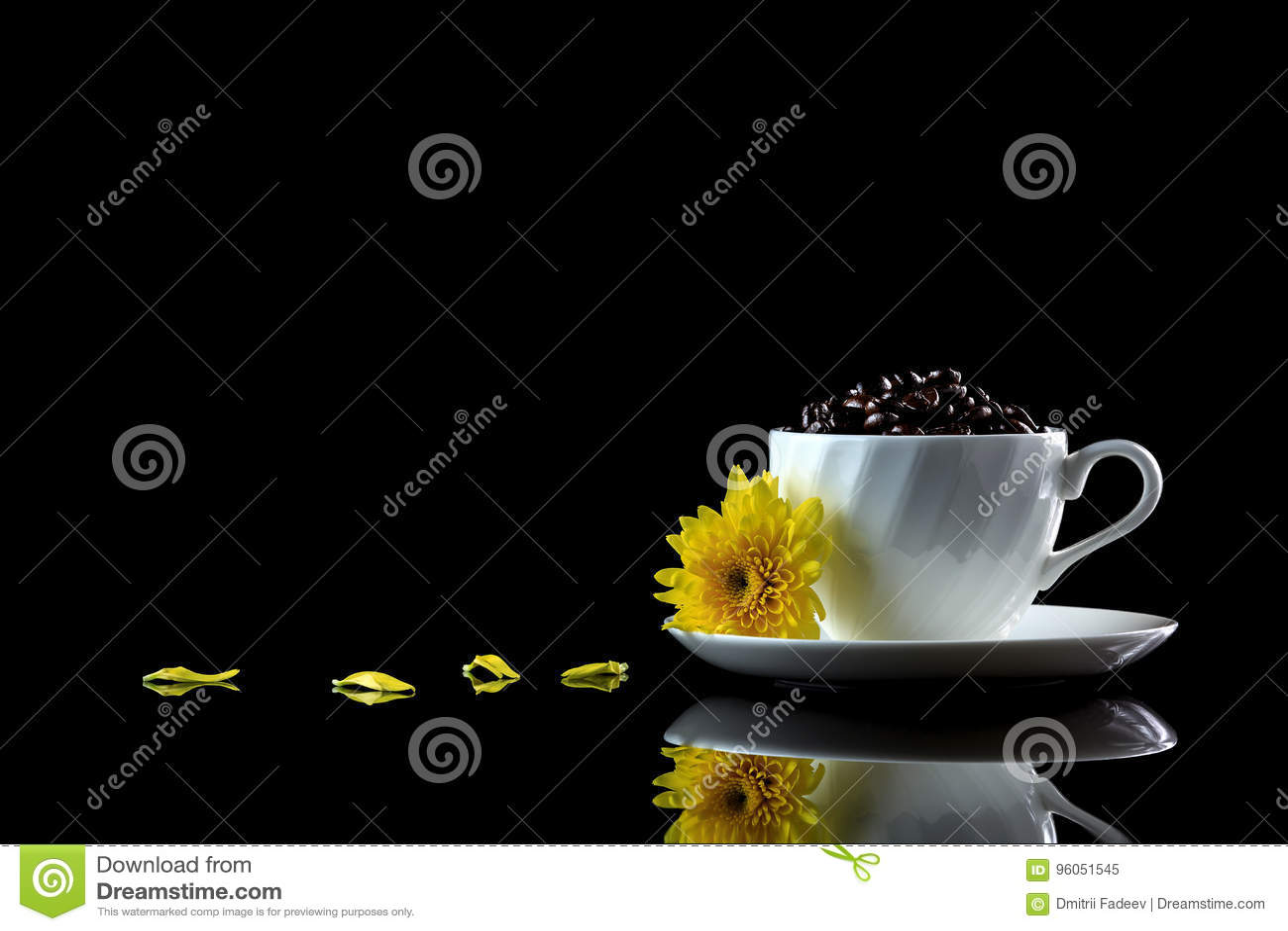 La tasse avec des grains de café et le chrysanthème jaune sur un noir se reflètent
