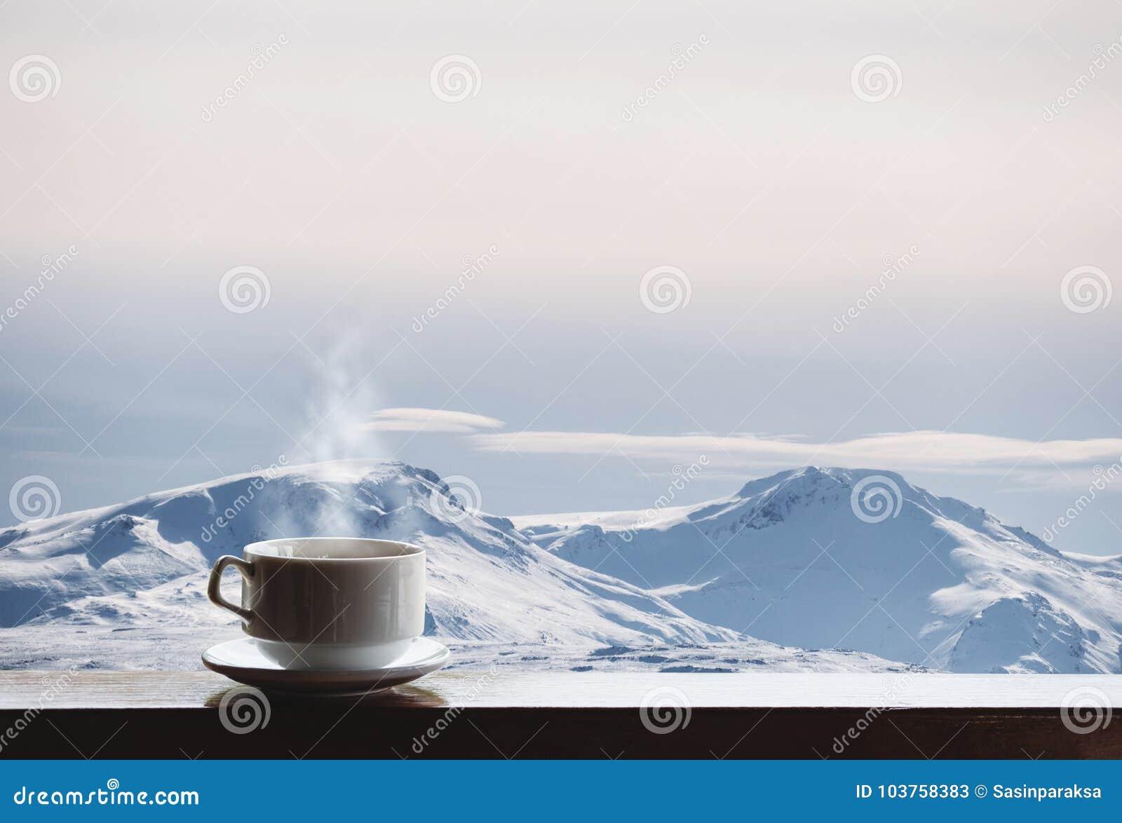 La tasse de la boisson chaude avec la vapeur sur le bureau et la neige en bois a couvert le Mountain View pendant le matin