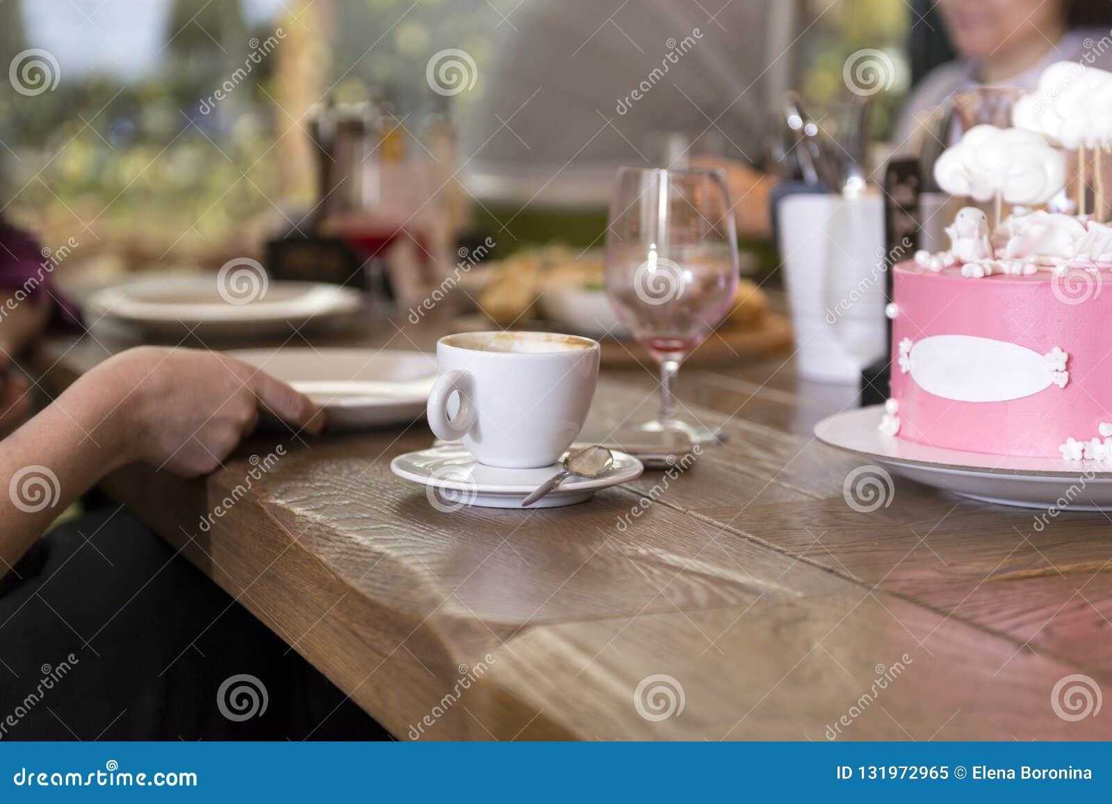 La tasse de café, le gâteau, les gens à la table de salle à manger en bois, a servi t