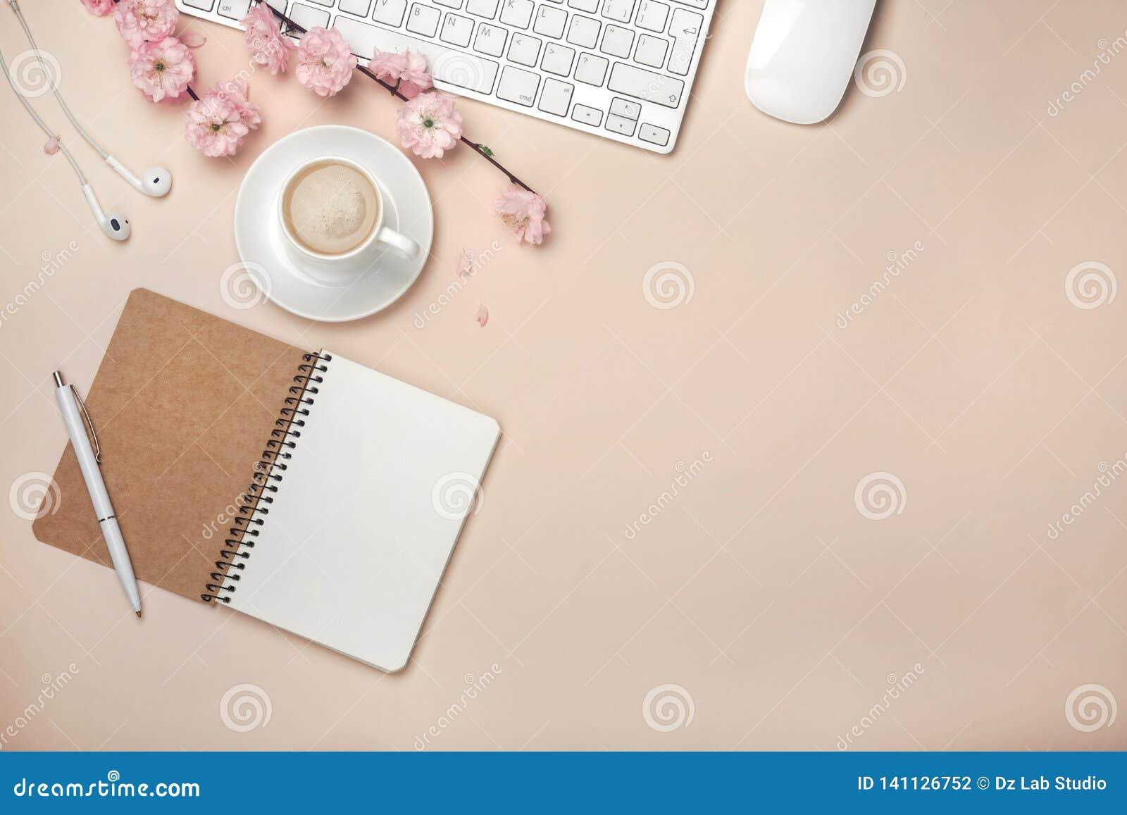 La taza blanca con el capuchino, Sakura florece, teclado, despertador, cuaderno en un fondo del rosa en colores pastel