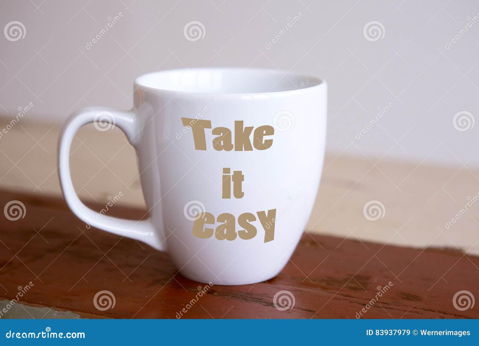 La taza blanca con las palabras lo toma fácil
