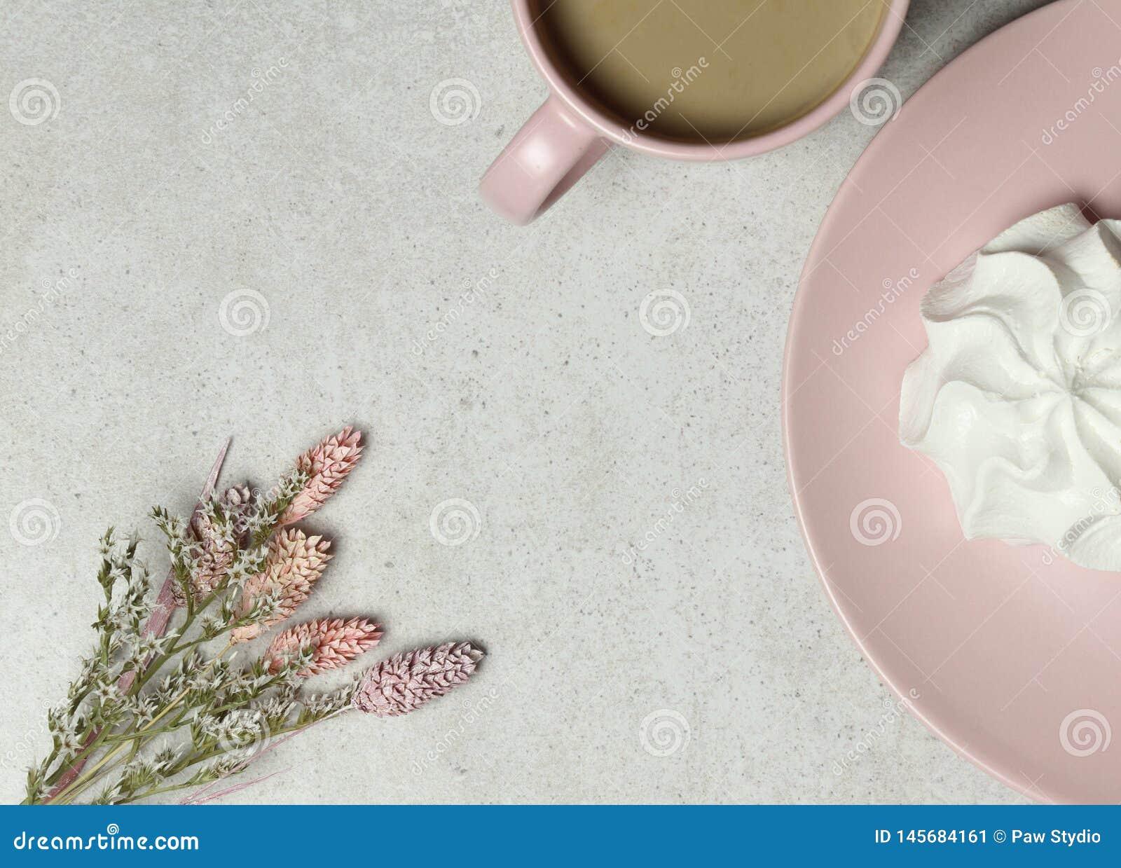 La taza de café, melcocha, ramo de flores blancas en la textura del granito