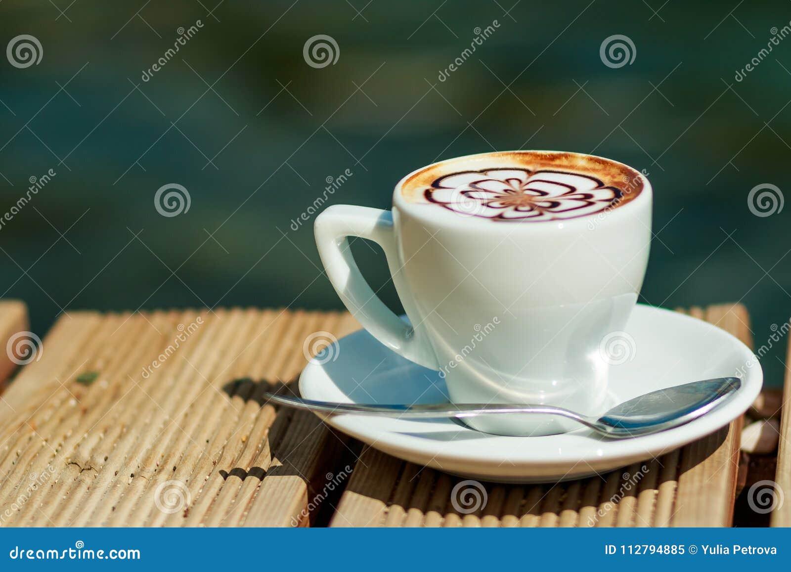 La taza de latte del arte en un café del capuchino aisló afuera, en la playa Café de la mañana taza blanca de café caliente del l
