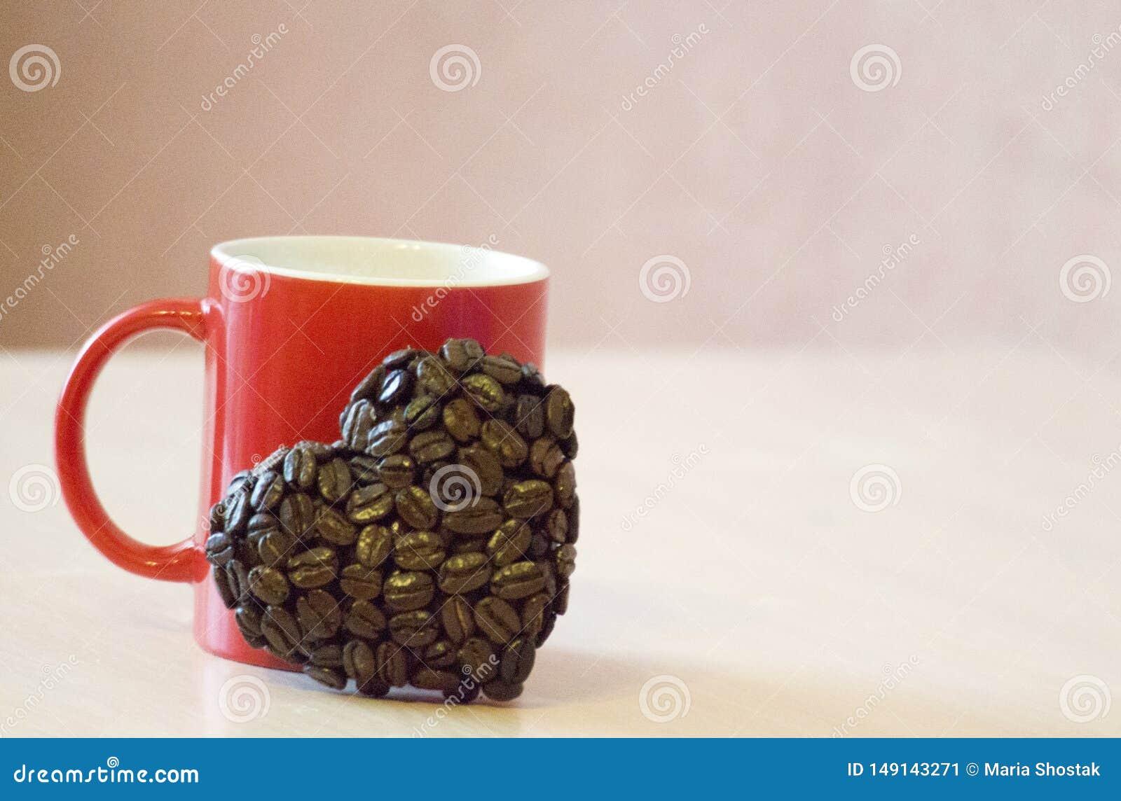 La taza roja se coloca en la tabla, cerca de la taza la forma de los granos de caf?, un s?mbolo del coraz?n del amor