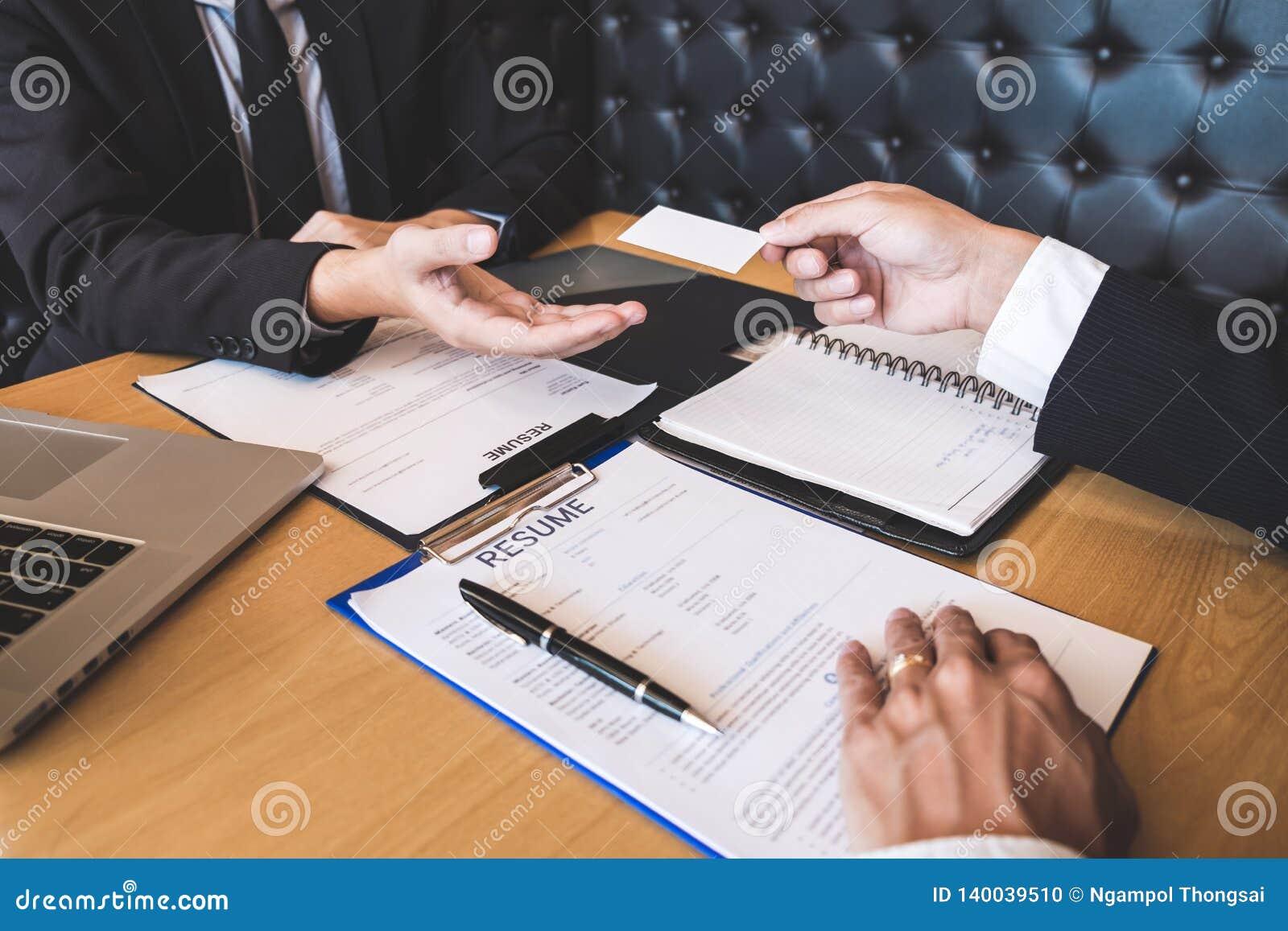 La tenencia del patrón o del reclutador que lee un curriculum vitae durante alrededor su perfil del candidato, patrón en traje es