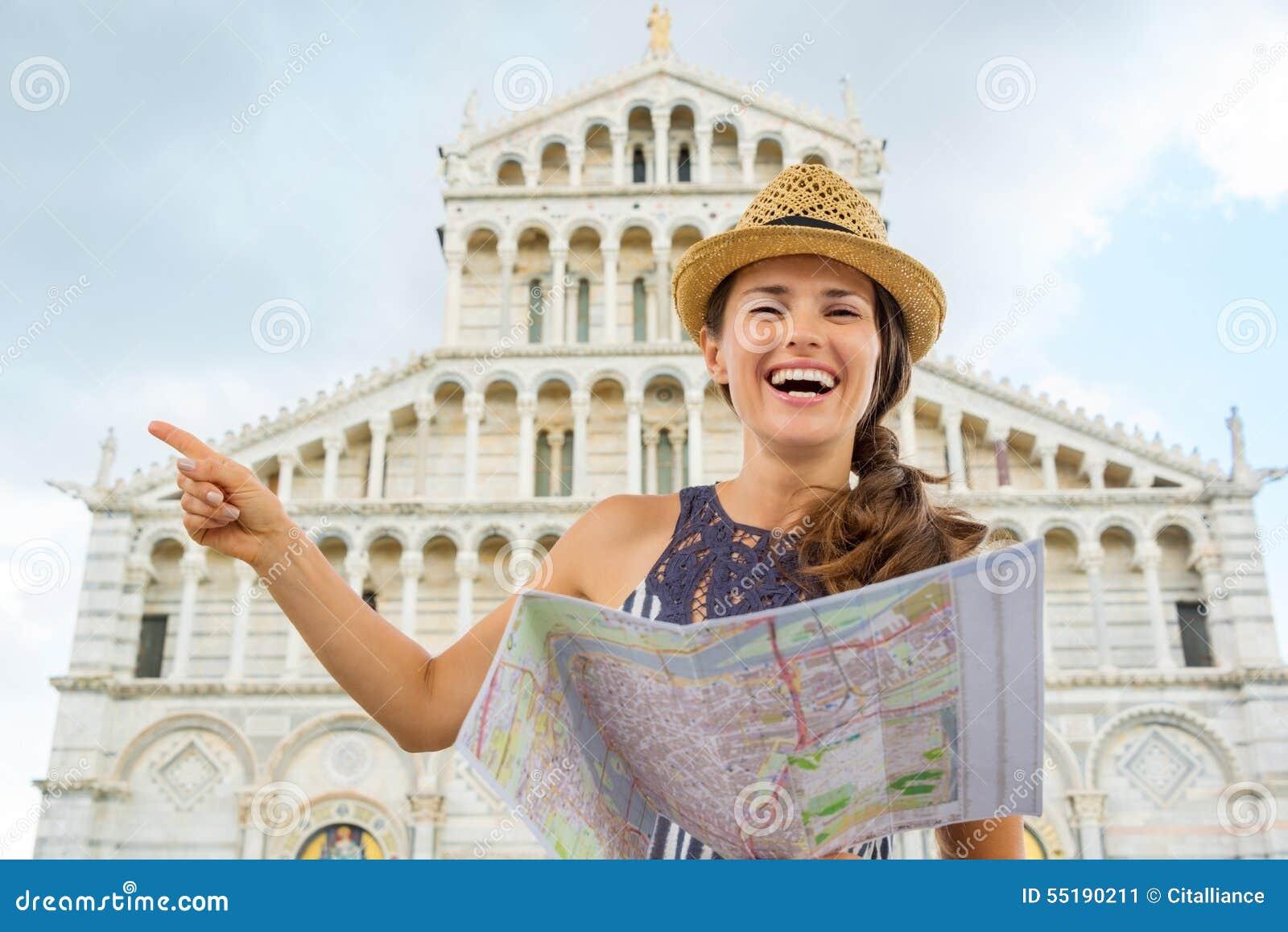 La tenencia turística sonriente de la mujer traza y señalando en Pisa