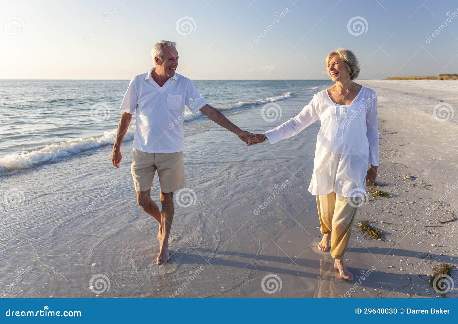 La tenuta di camminata delle coppie senior felici passa la spiaggia tropicale