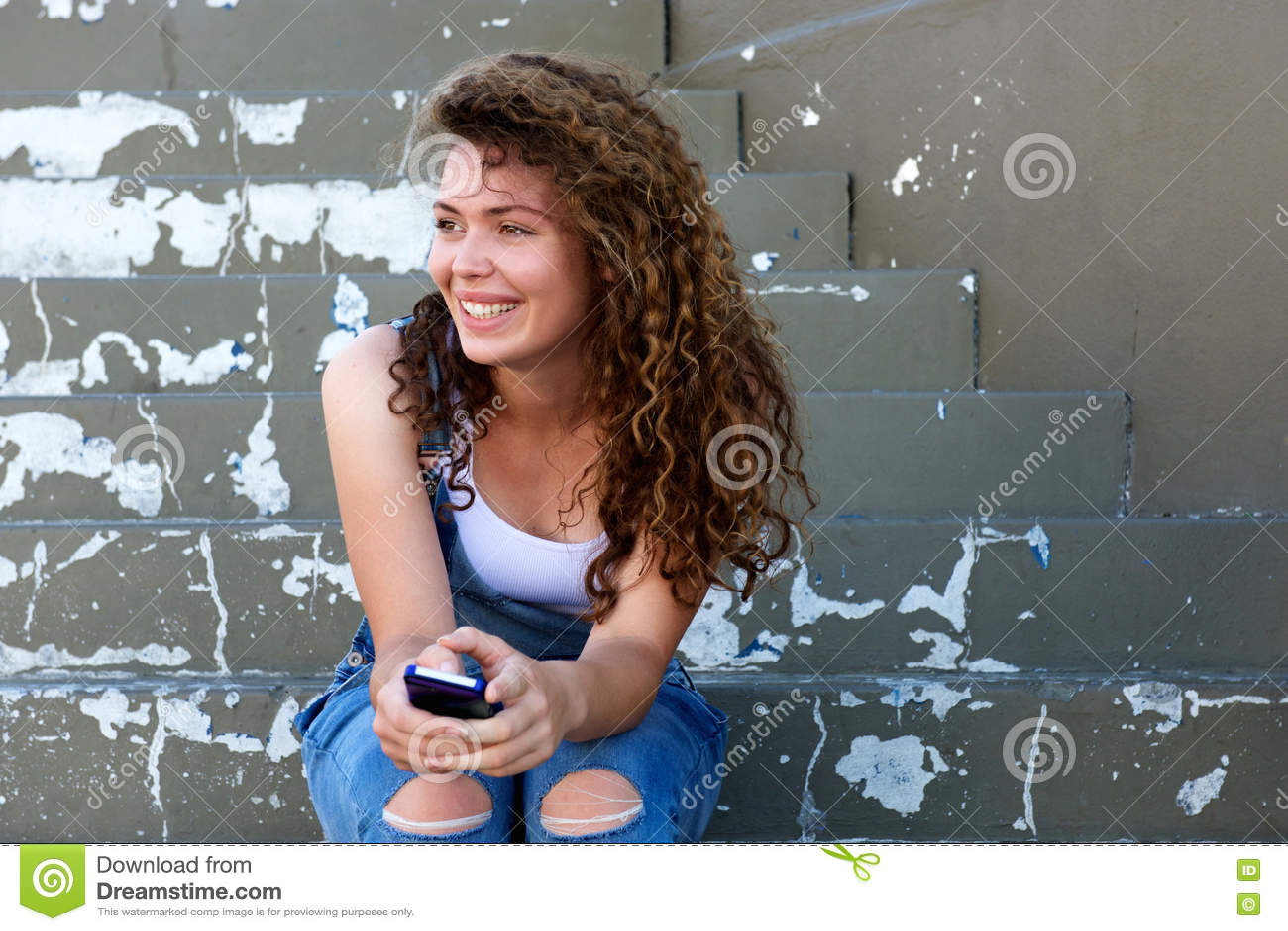 La tenuta teenager sorridente della ragazza telefona e seduta sui punti
