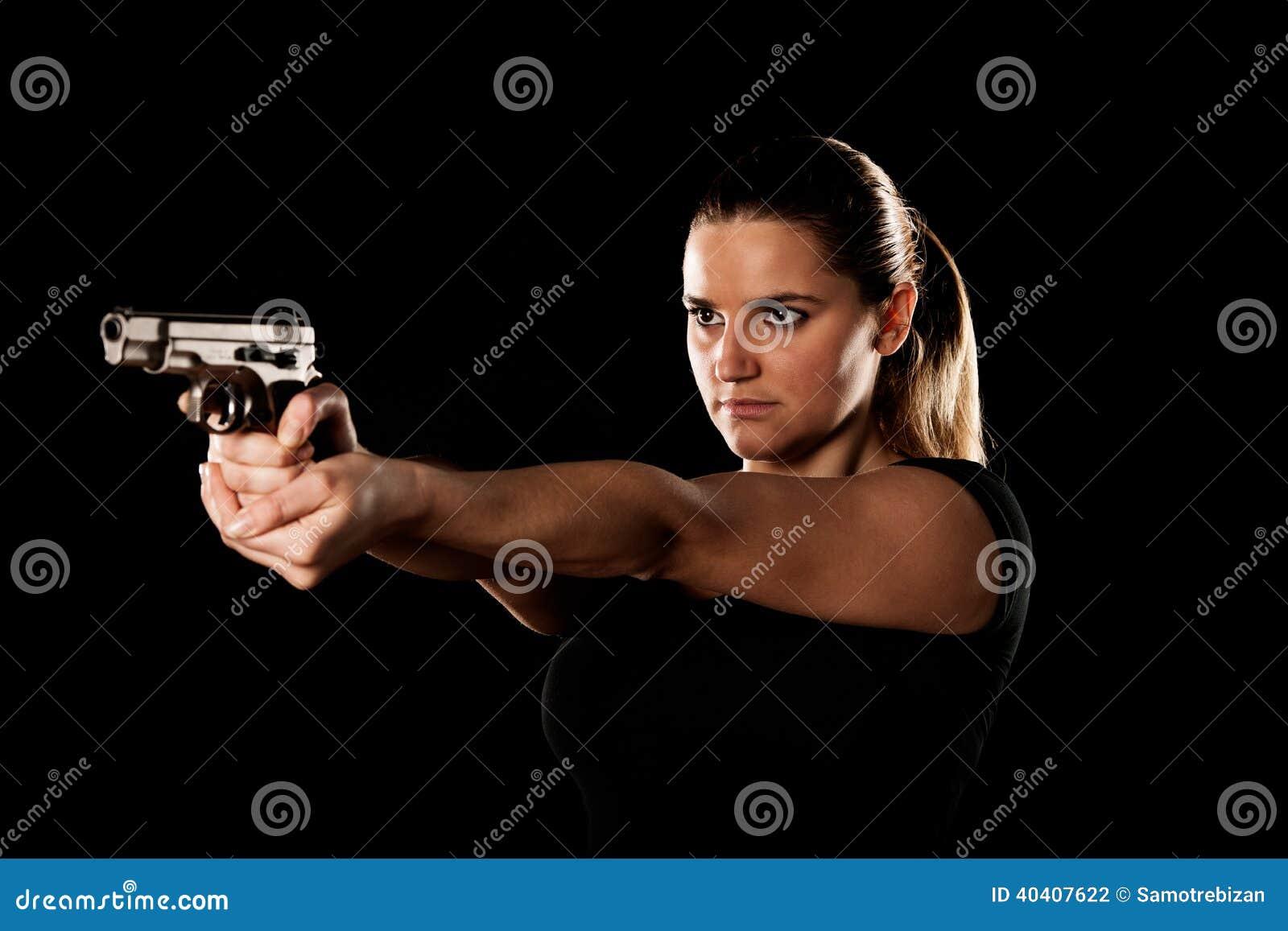 La terroriste dangereuse de femme s est habillée dans le noir avec une arme à feu dans son Han
